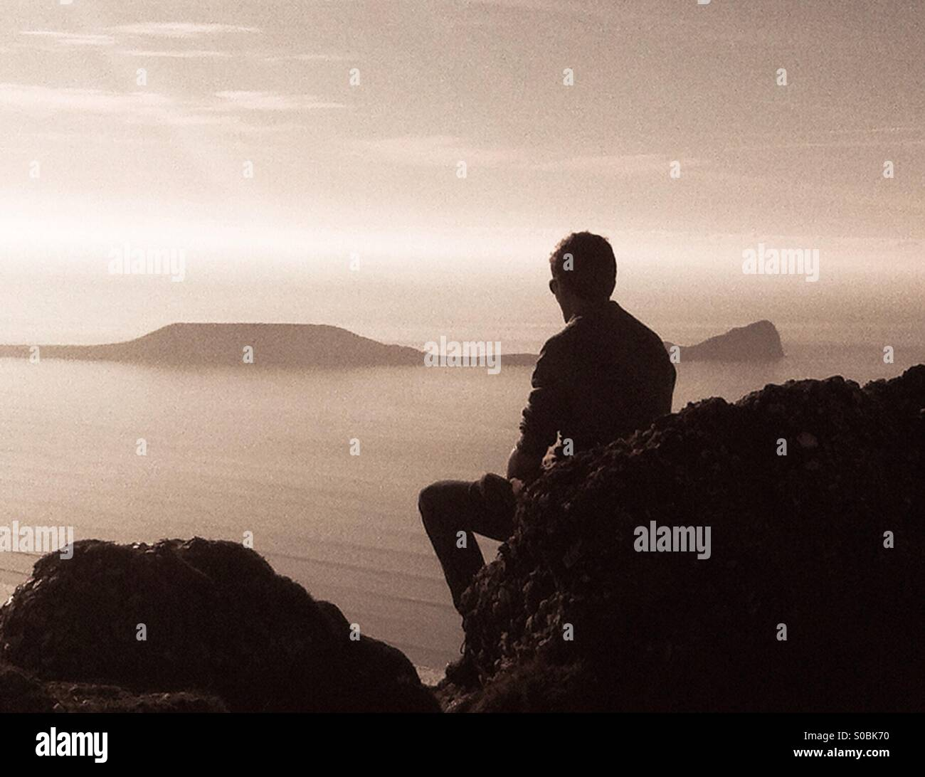 Ragazzo seduto su una roccia che si affaccia sul mare nei pressi di Worms testa, Gower. Vista laterale silhouette. Immagini Stock