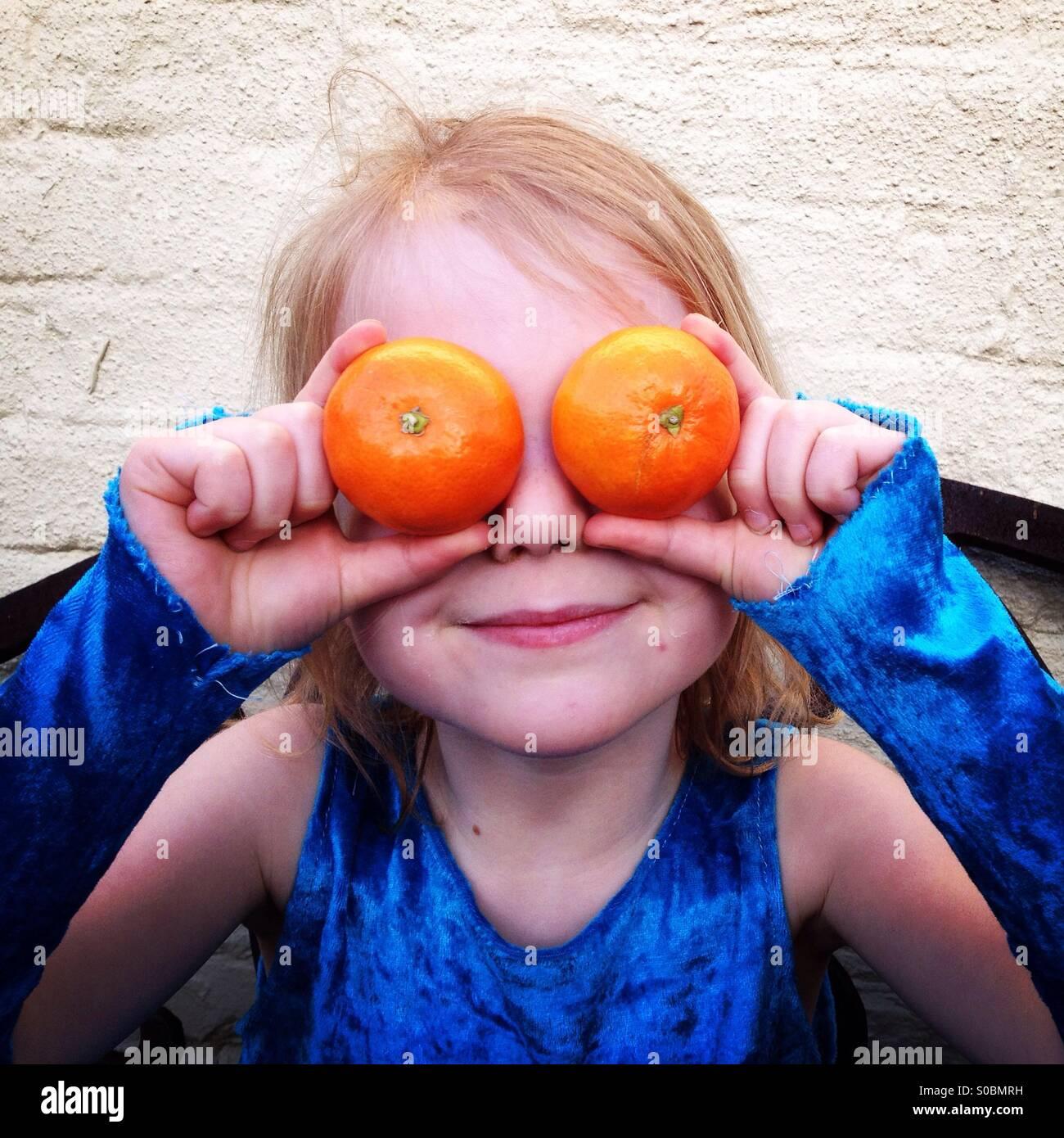 Bambino felice con le arance come gli occhi. Ragazza con troppo morbidi arance oltre i suoi occhi. Immagini Stock