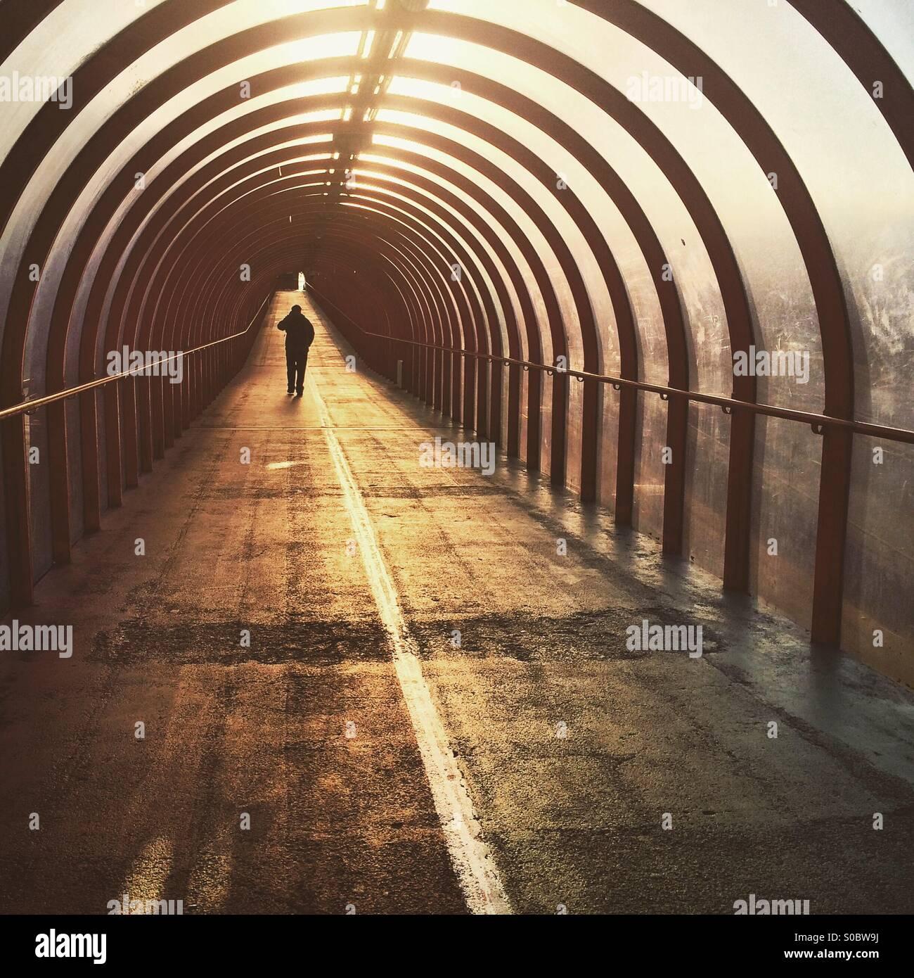 Una silhouette di un uomo che cammina verso il basso un tunnel a sunrise in Glasgow Foto Stock