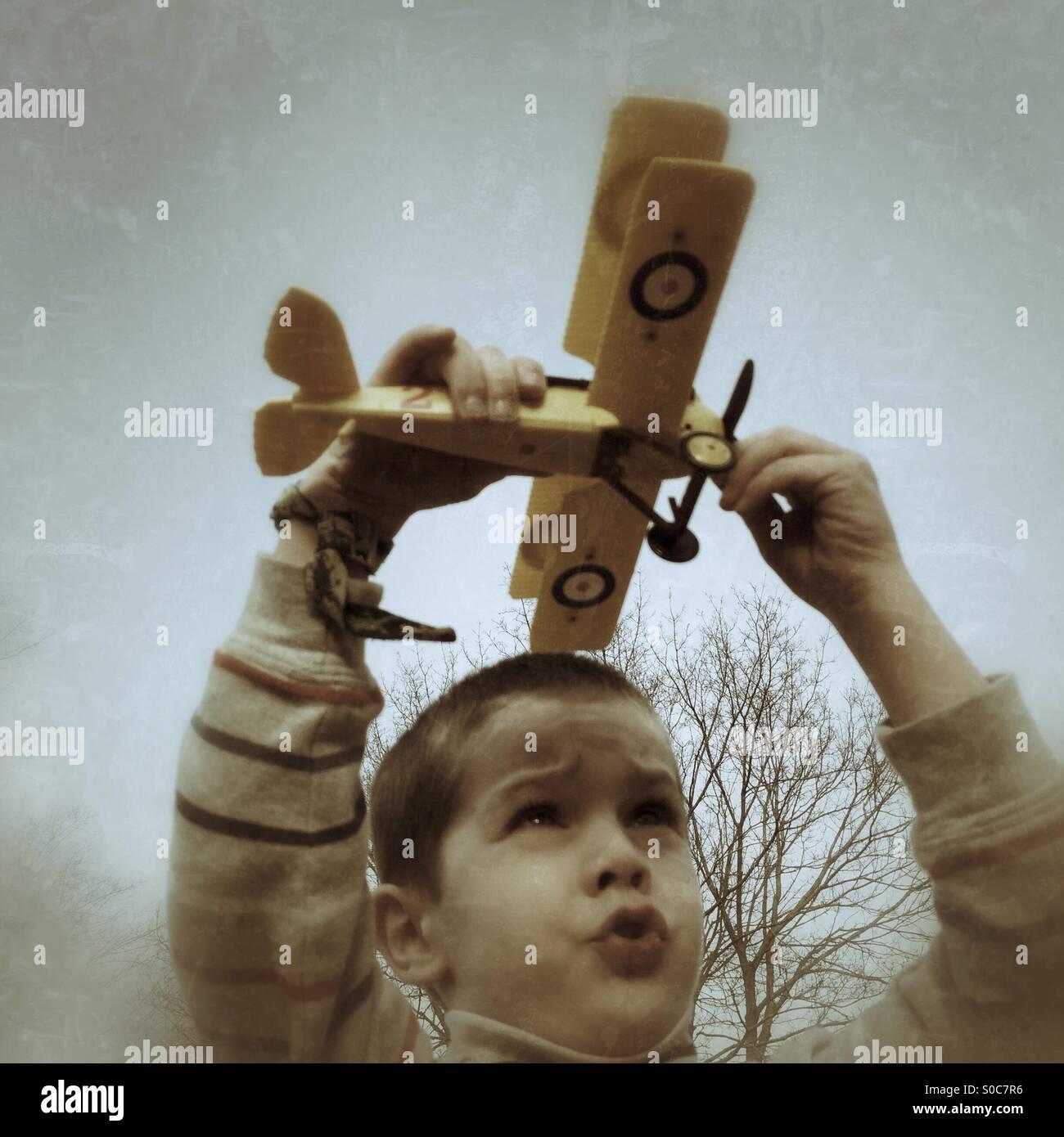 Giovane ragazzo giocando con il modello di un biplano Immagini Stock
