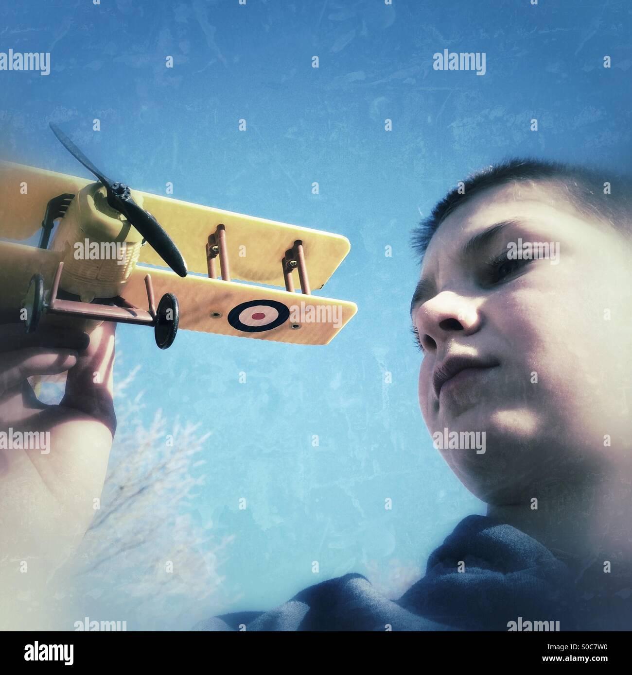 Guardando verso l'alto un ragazzo tenendo il suo modello aereo Immagini Stock