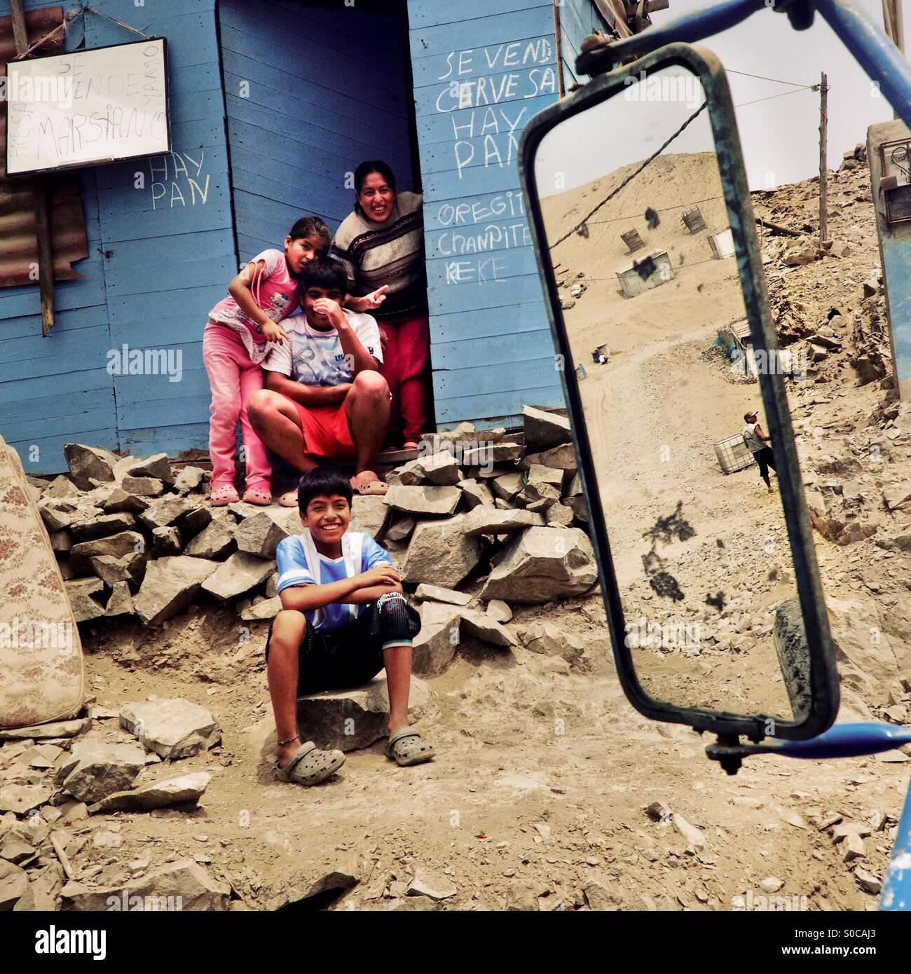 Famiglia Peruviana membri siedono davanti a una casa in legno sulla polvere della collina di Pachacútec, un deserto Foto Stock