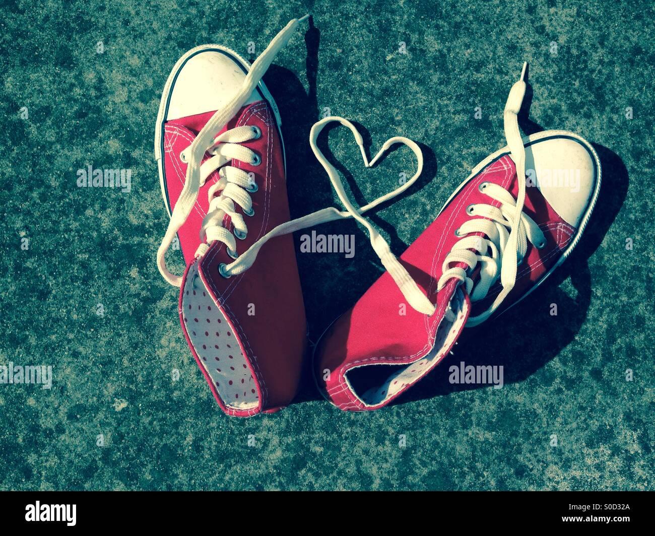 L amore del cuore sui lacci delle scarpe sportive forma di cuore rosso stivali di baseball Immagini Stock