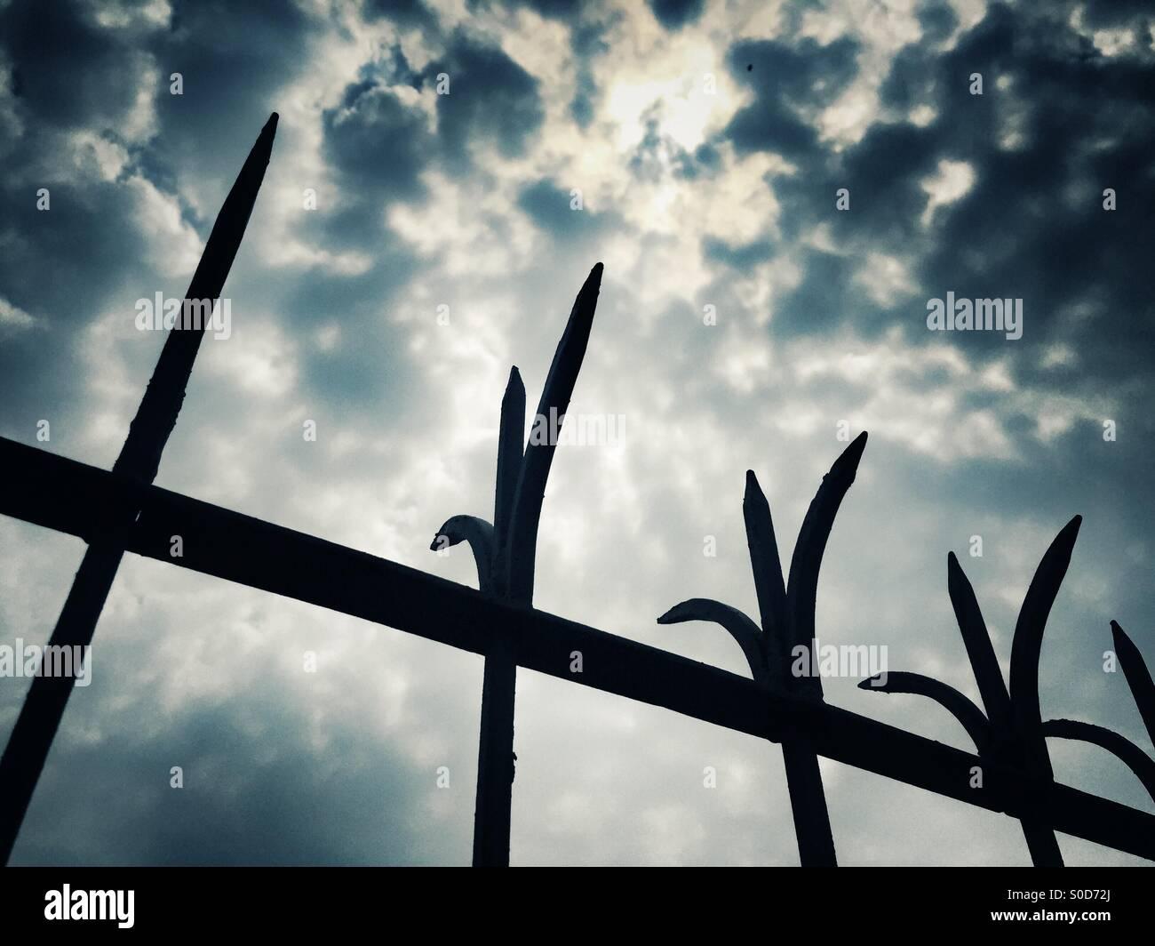 Recinzioni di filo spinato contro il cielo drammatico Immagini Stock