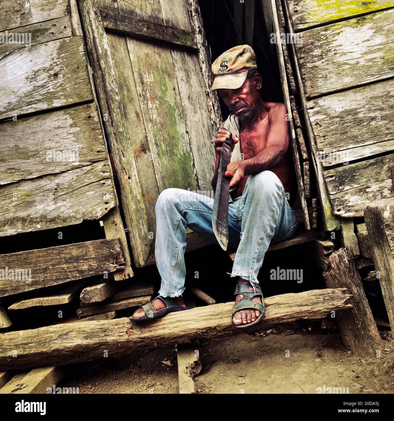 Un contadino panamense controlla la nitidezza del machete lama mentre si siede alla porta della sua casa a Boca Immagini Stock