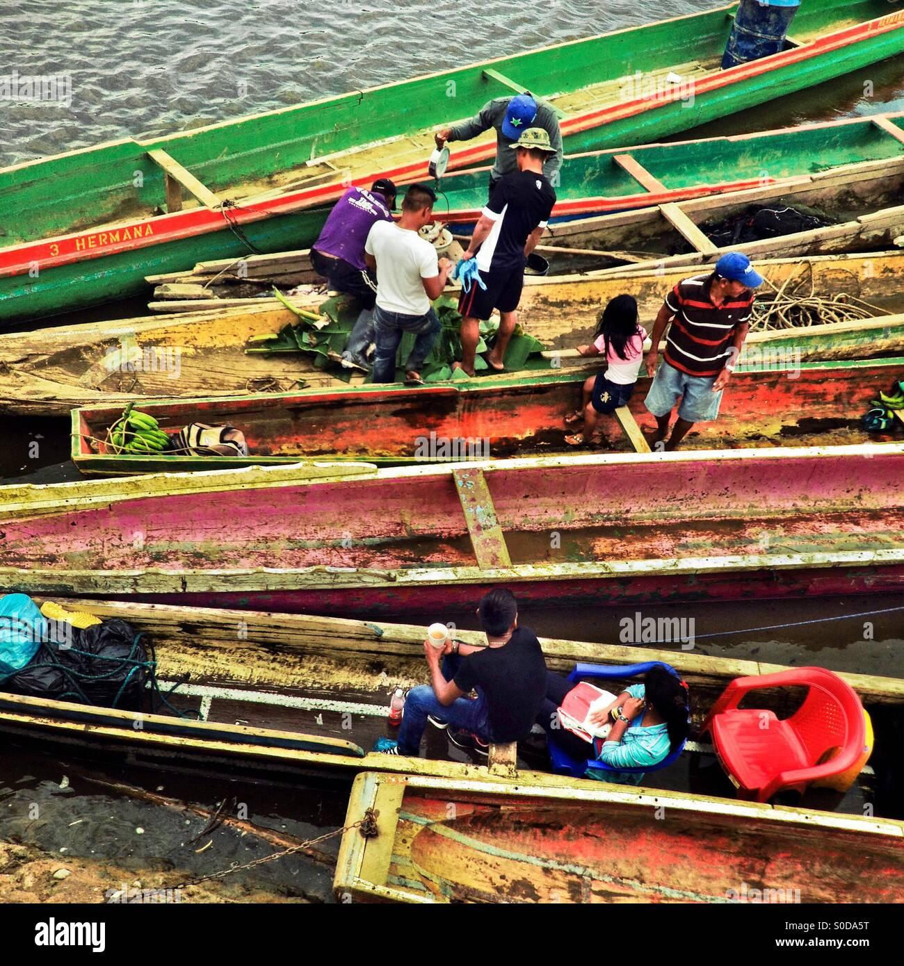 Gli abitanti di un villaggio panamense vendere pesce e banane all'interno delle canoe ancorato sul lungofiume Immagini Stock