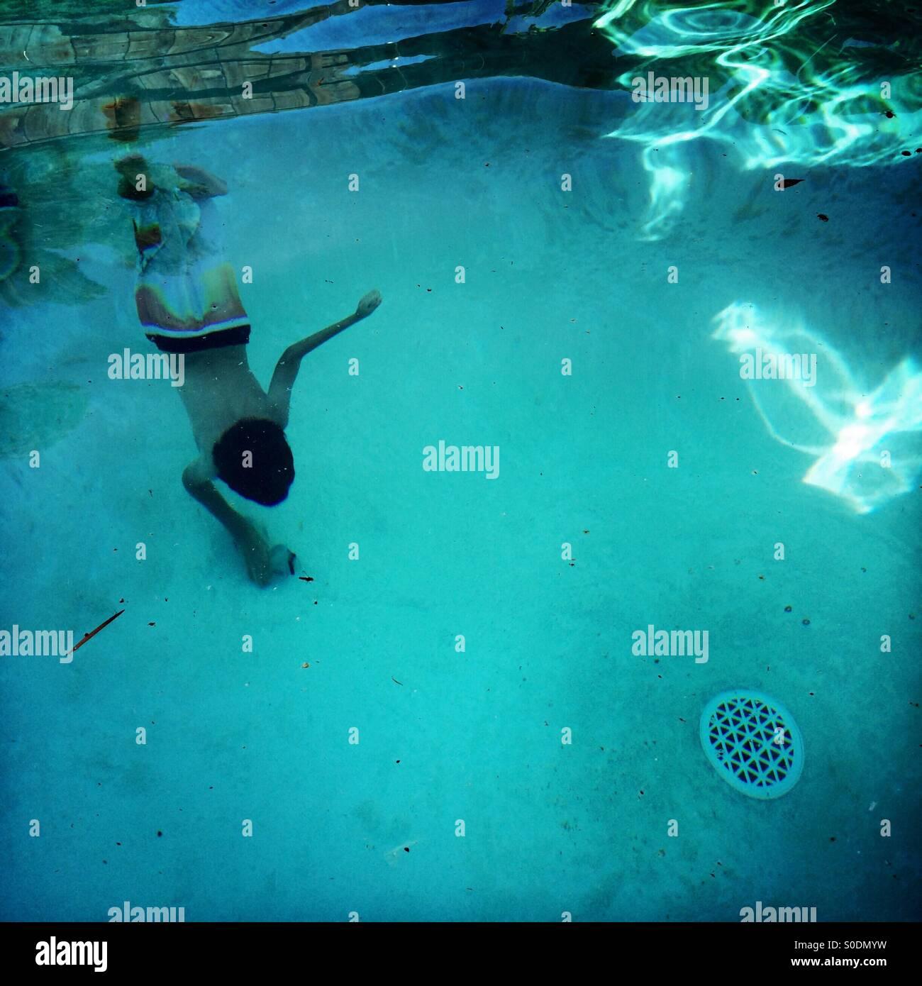A sette anni di vecchio ragazzo si tuffa al fondo di una piscina per ottenere la sua maschera subacquea. Immagini Stock