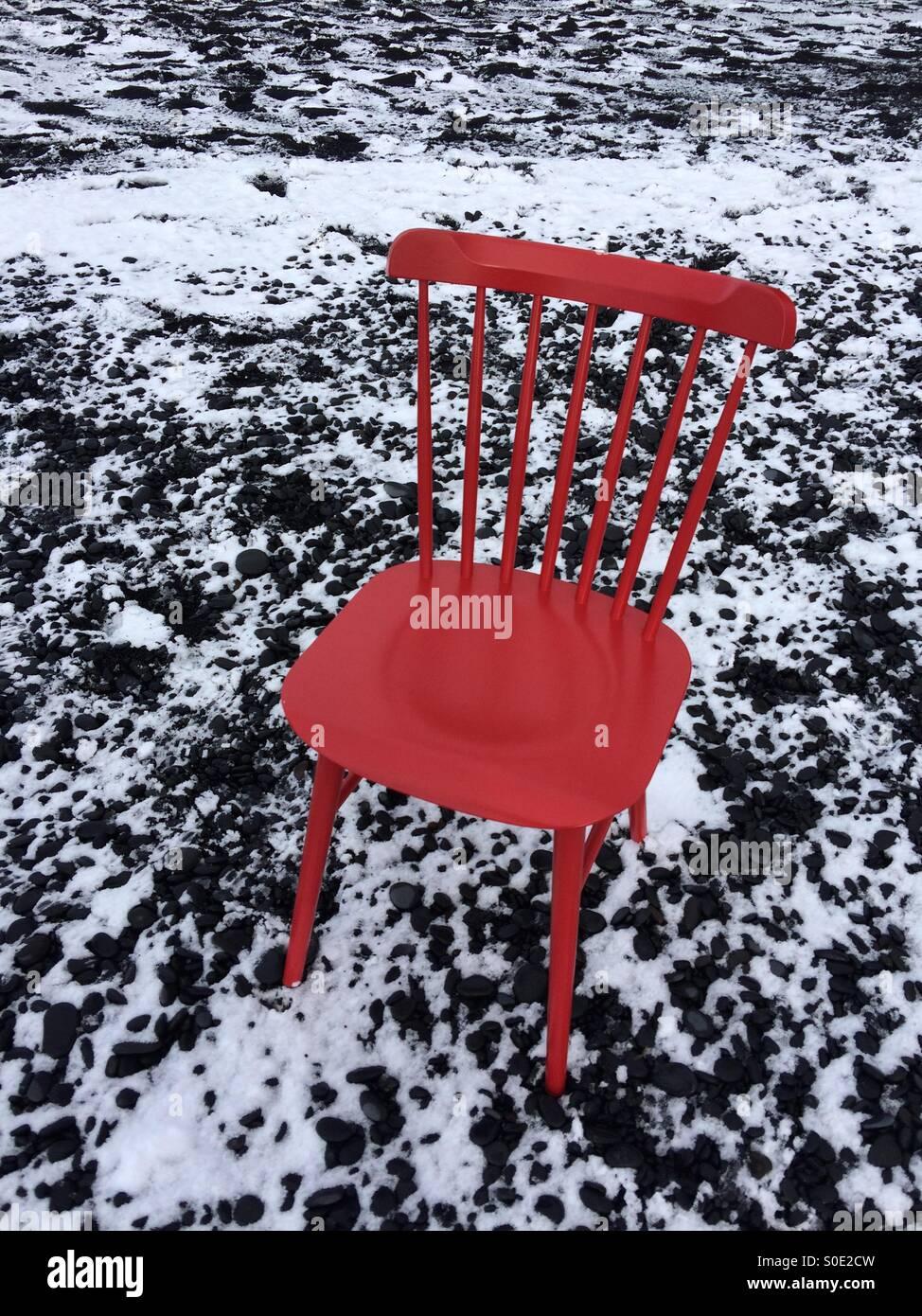 Sedia rossa nella spiaggia di sabbia nera. L'Islanda Foto