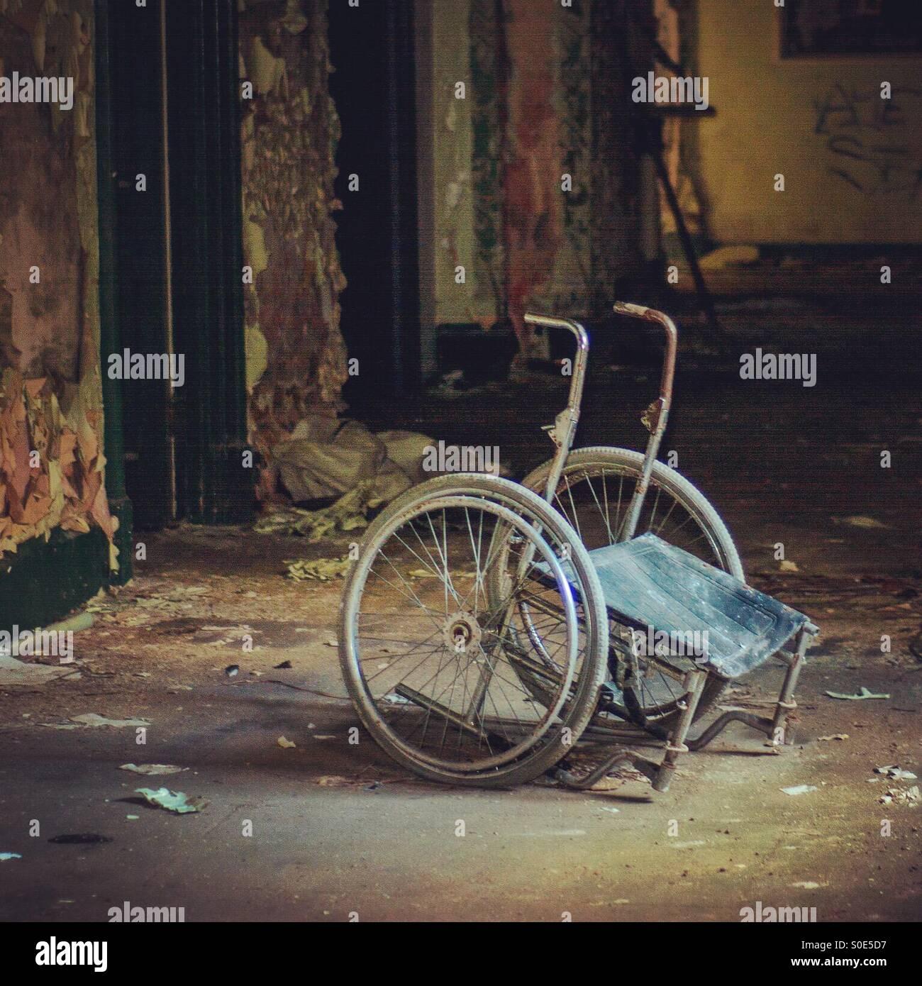 Lugubre la sedia a rotelle in edificio abbandonato Immagini Stock
