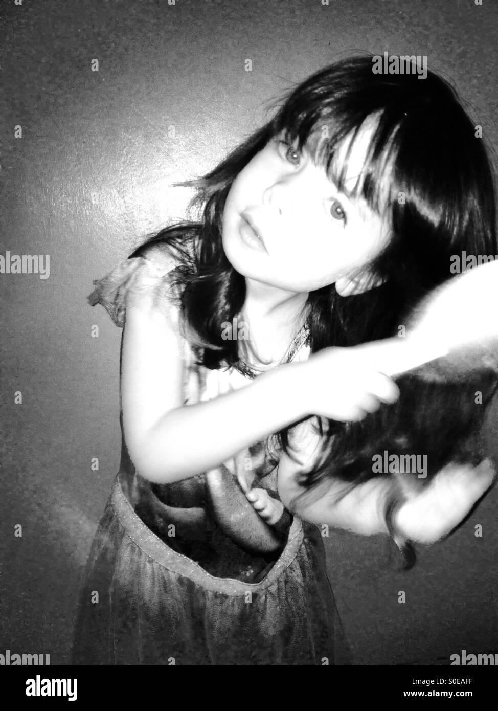 3 anno vecchia ragazza spazzolando i suoi capelli lunghi Immagini Stock