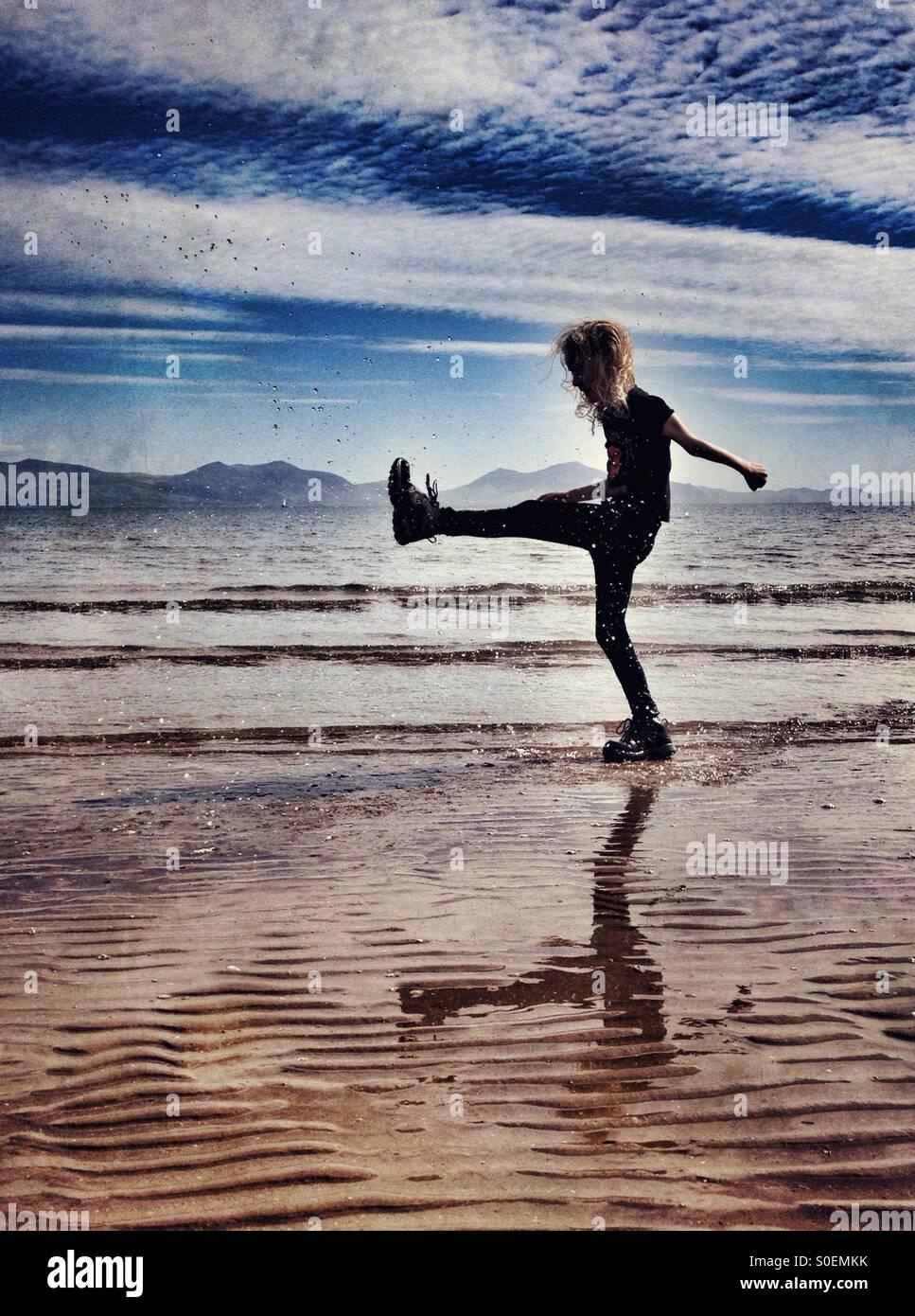 Ragazza giovane giocando in mare a Newborough sulla spiaggia di Anglesey Immagini Stock