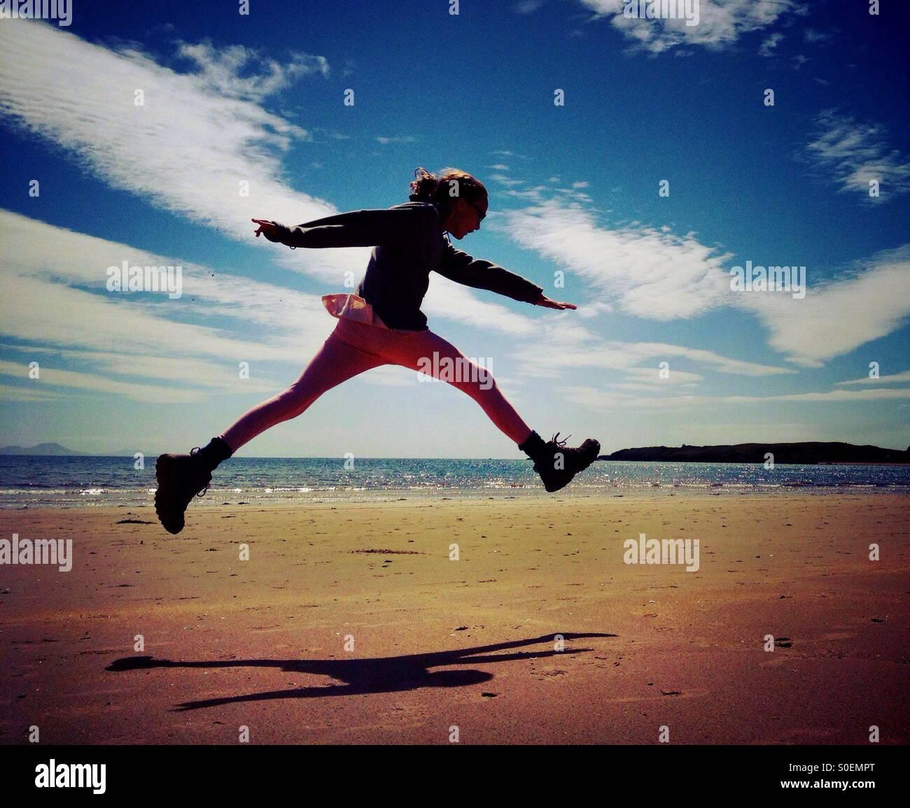 Giovane ragazza che saltava per la gioia sulla spiaggia di Newborough su Anglesey Immagini Stock