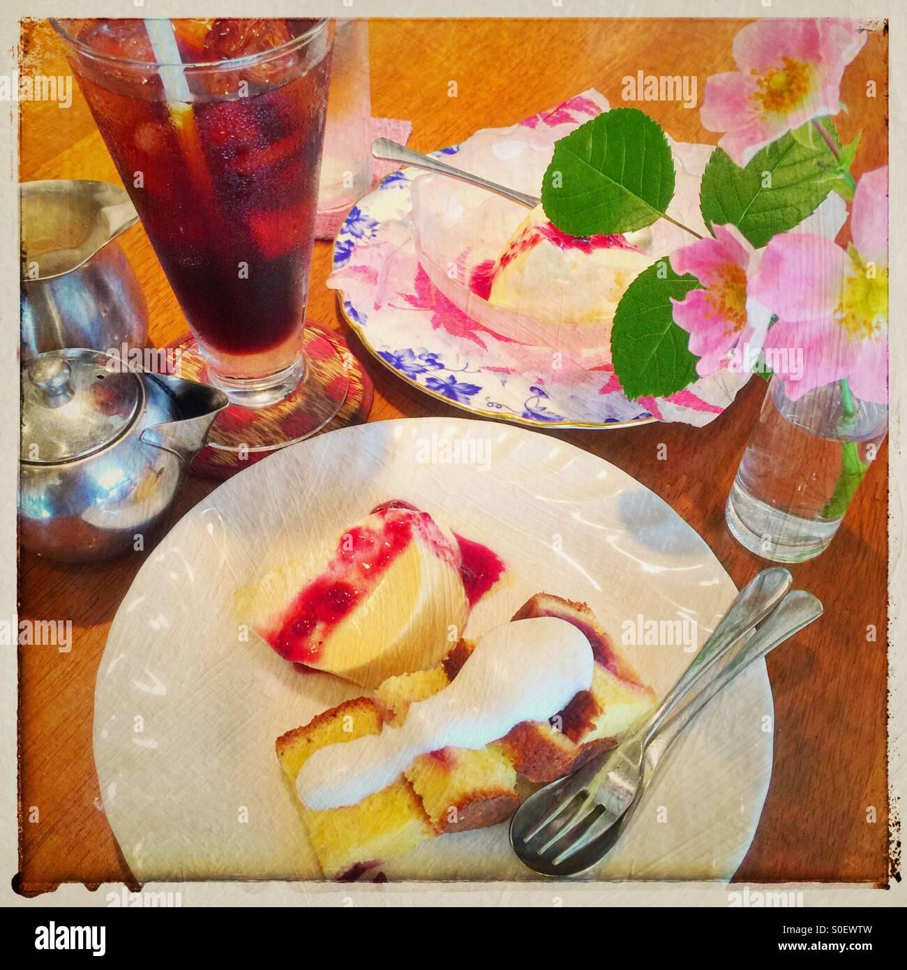 Il tè del pomeriggio con caffè ghiacciato, crema bavarese con salsa di mirtilli, sterlina la torta con panna montata topping e vaso di wild rose rosa. Telaio vintage e texture pittorica di sovrapposizione. Foto Stock