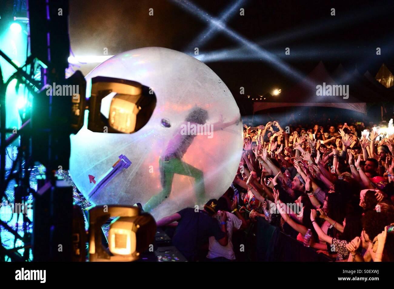 Il Flaming Lips Wayne Coyne testa fuori in mezzo alla folla nella sua firma 'hamster ball' durante la levitazione Immagini Stock