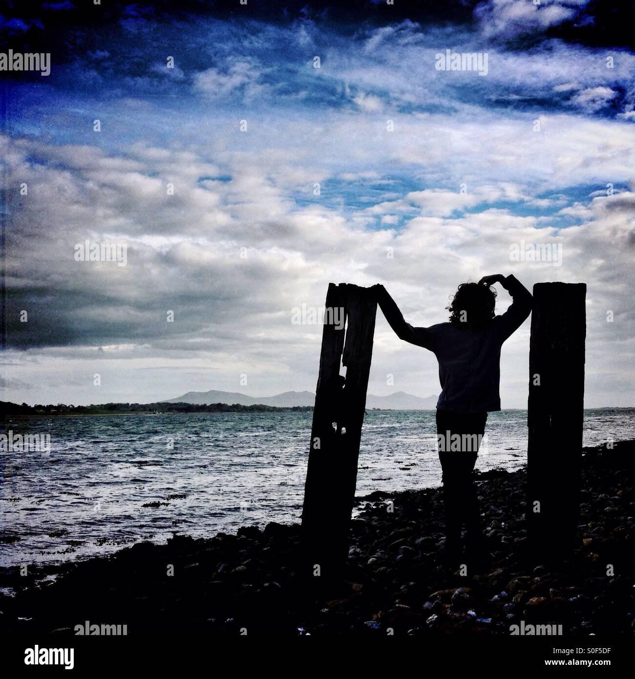 Giovane ragazza che pongono tra due montanti in legno in silhouette sulla spiaggia ghiaiosa Immagini Stock