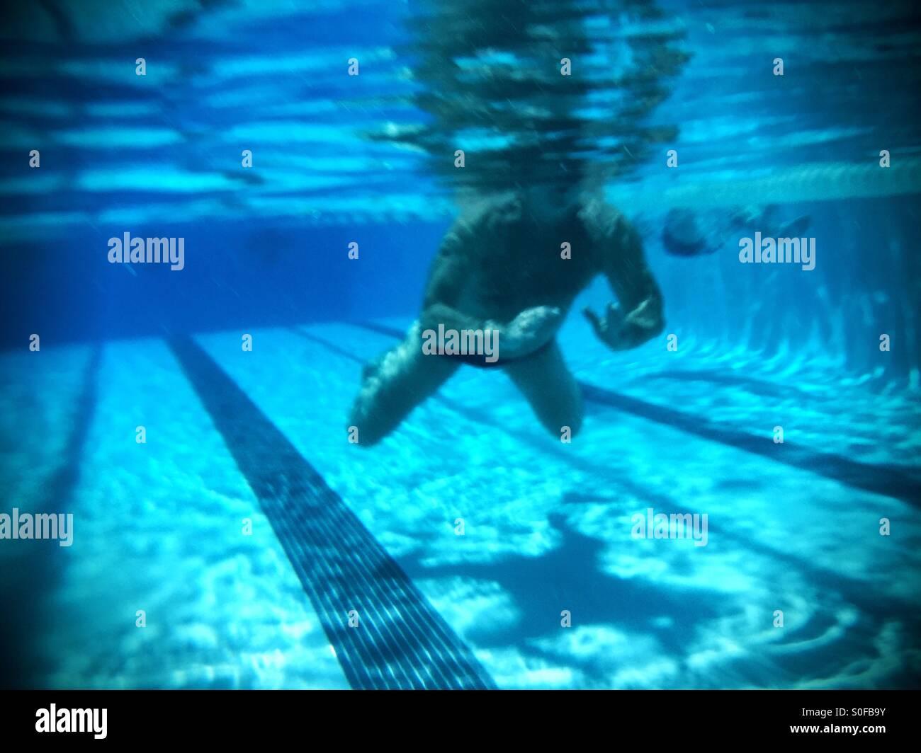 Nuotatore nuoto a rana vista subacquea con ombra acquosa, riflessioni. Immagini Stock