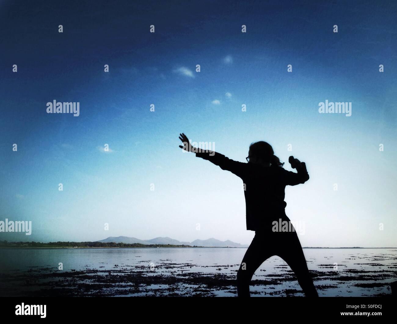 Giovane ragazza si prepara a lanciare una pietra da Menai Strait su Anglesey Immagini Stock