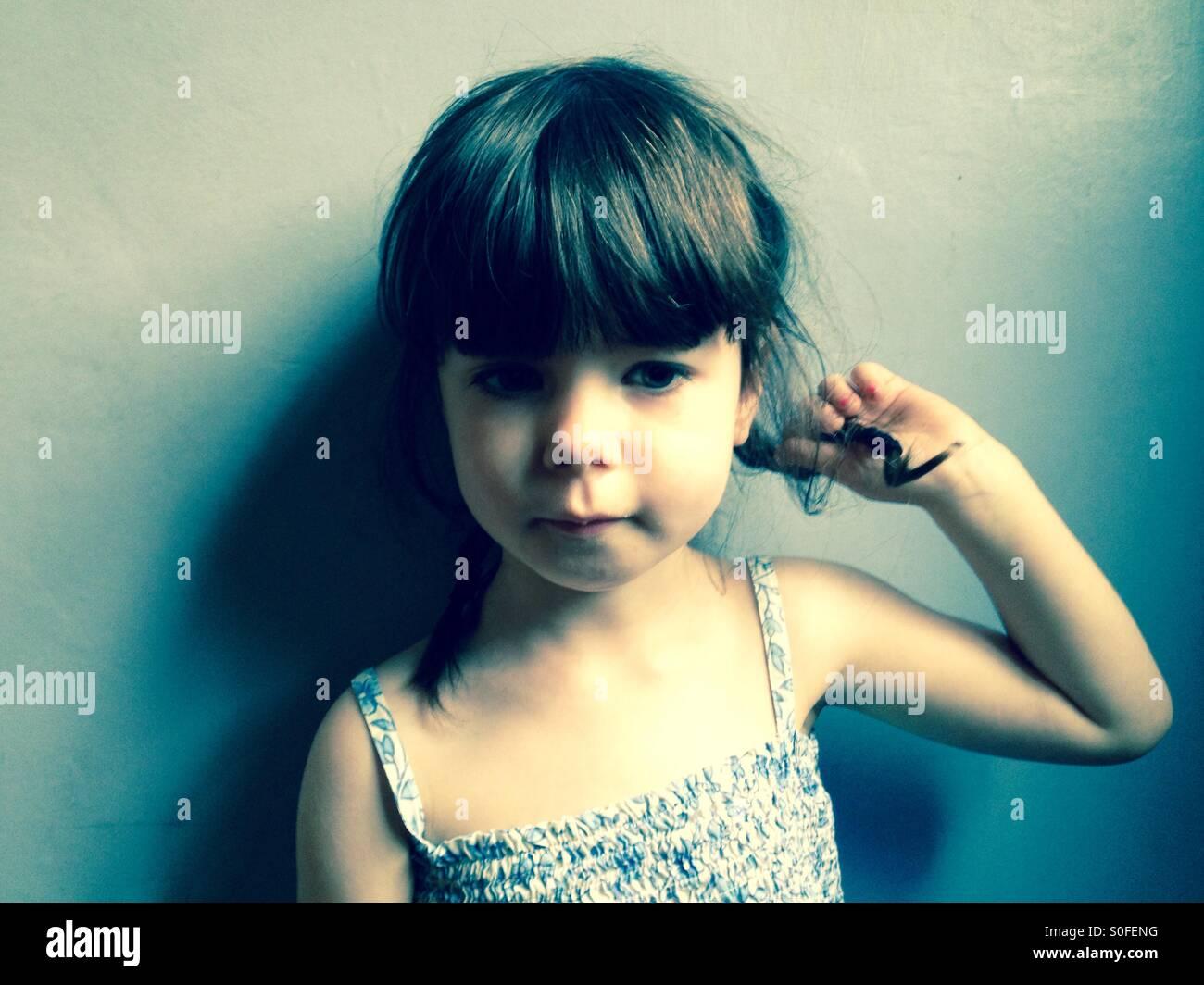 3 anno vecchia ragazza a giocare con i suoi capelli Immagini Stock
