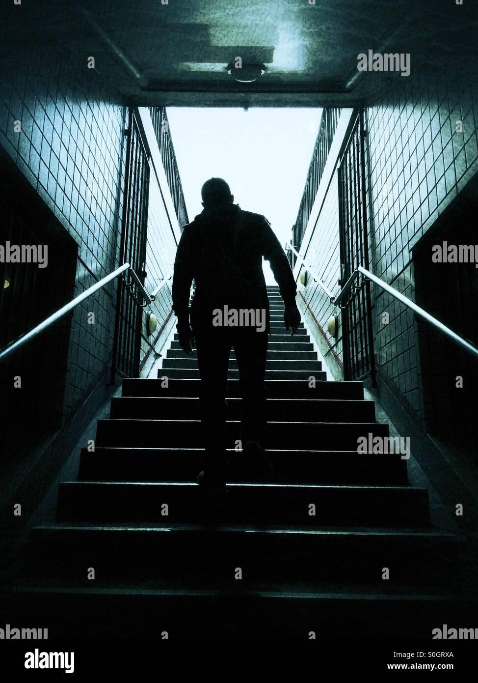 Uomo che cammina su per le scale Immagini Stock