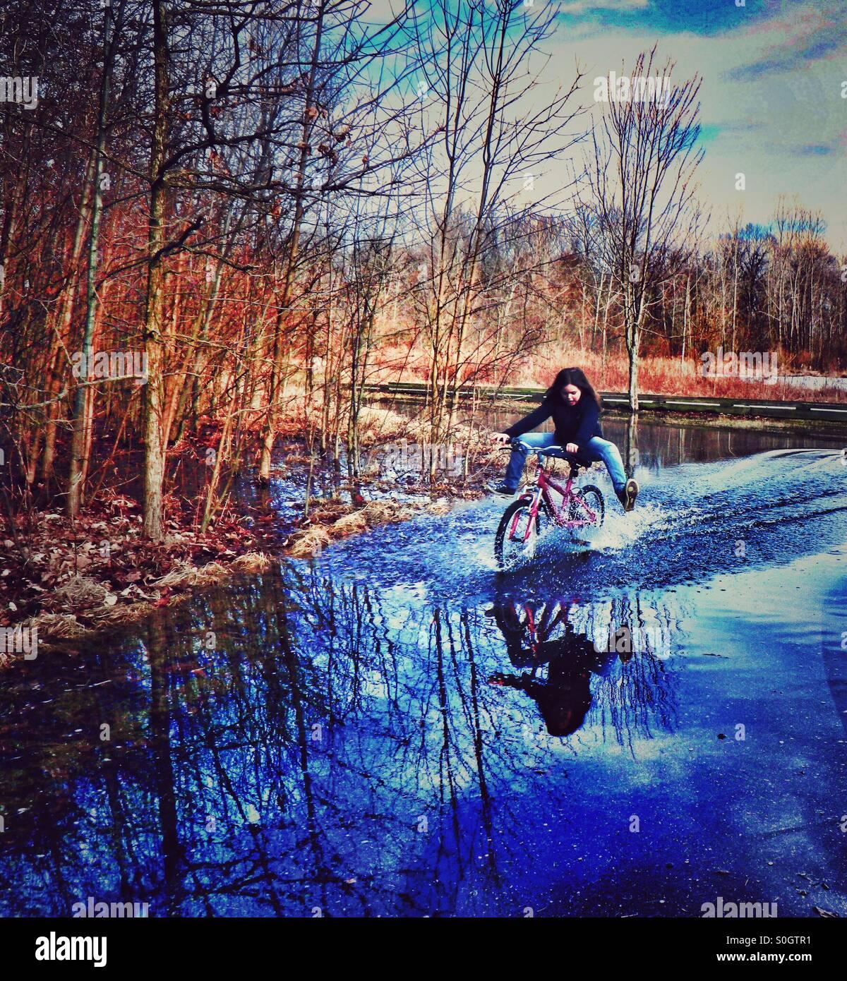 Ragazza cavalcare la sua bicicletta Immagini Stock