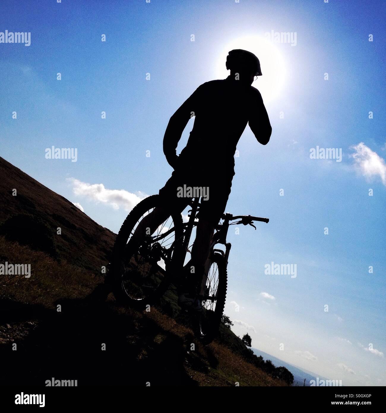 Silhouette di uomo con mountain bike Immagini Stock