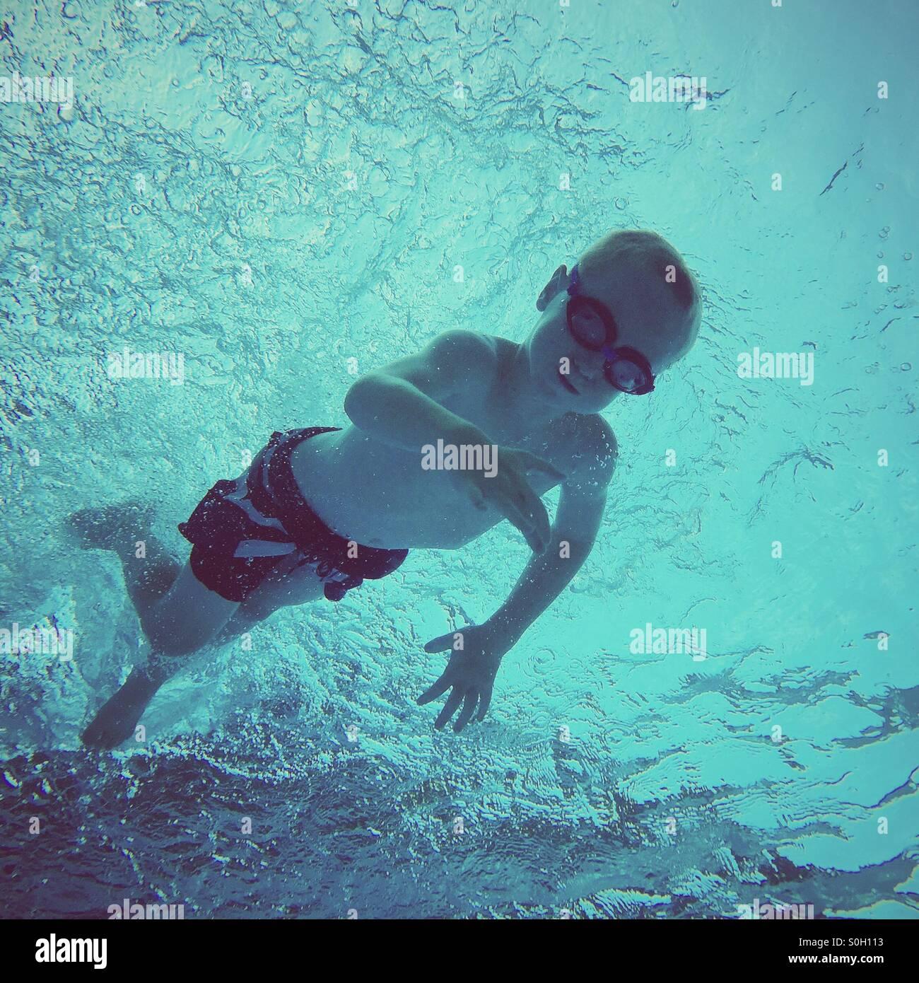 Riprese subacquee di un giovane ragazzo che nuotano verso la superficie dell'acqua, girato da sotto. Immagini Stock