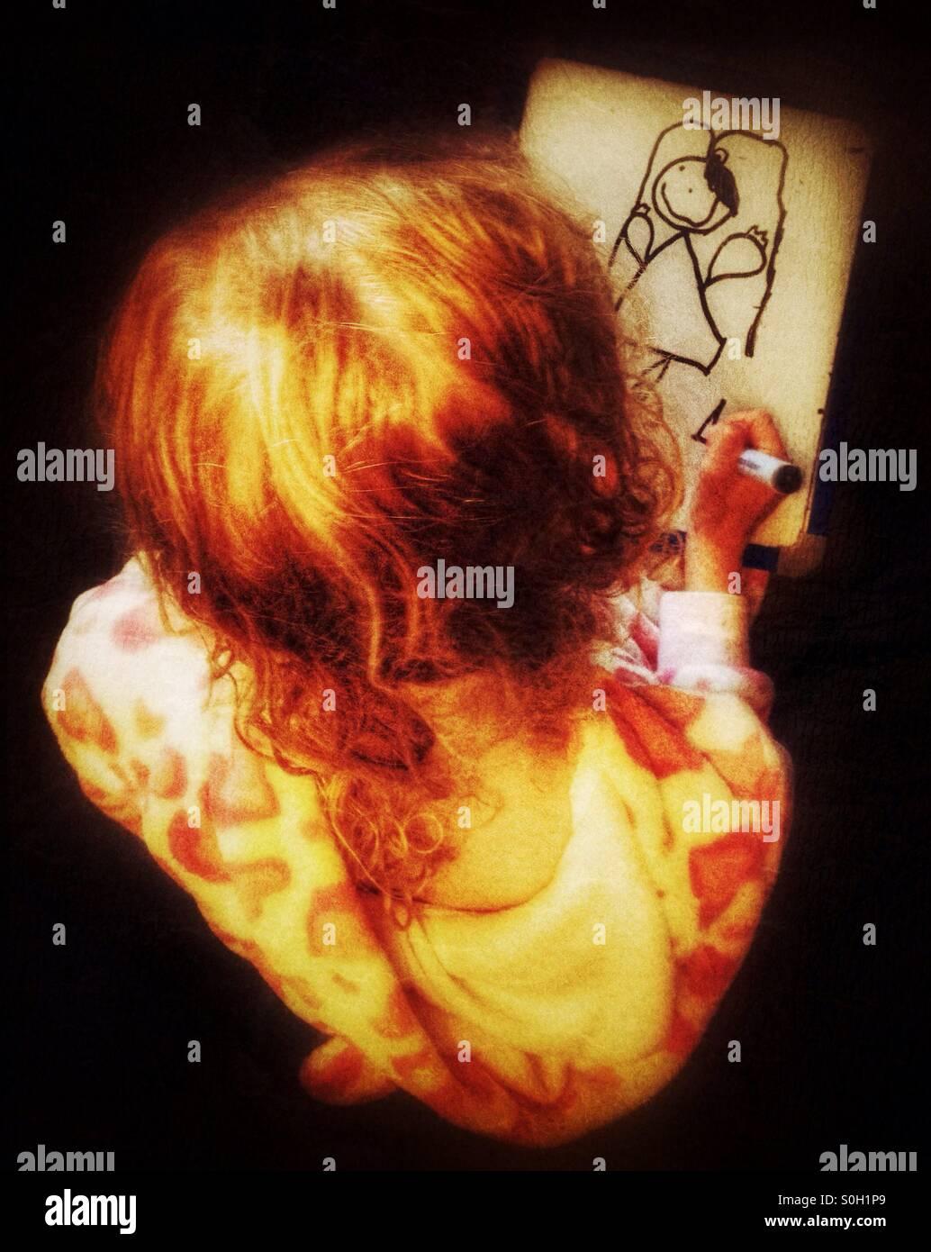 Giovane ragazza il disegno di una giovane ragazza su una piccola scheda bianca Immagini Stock