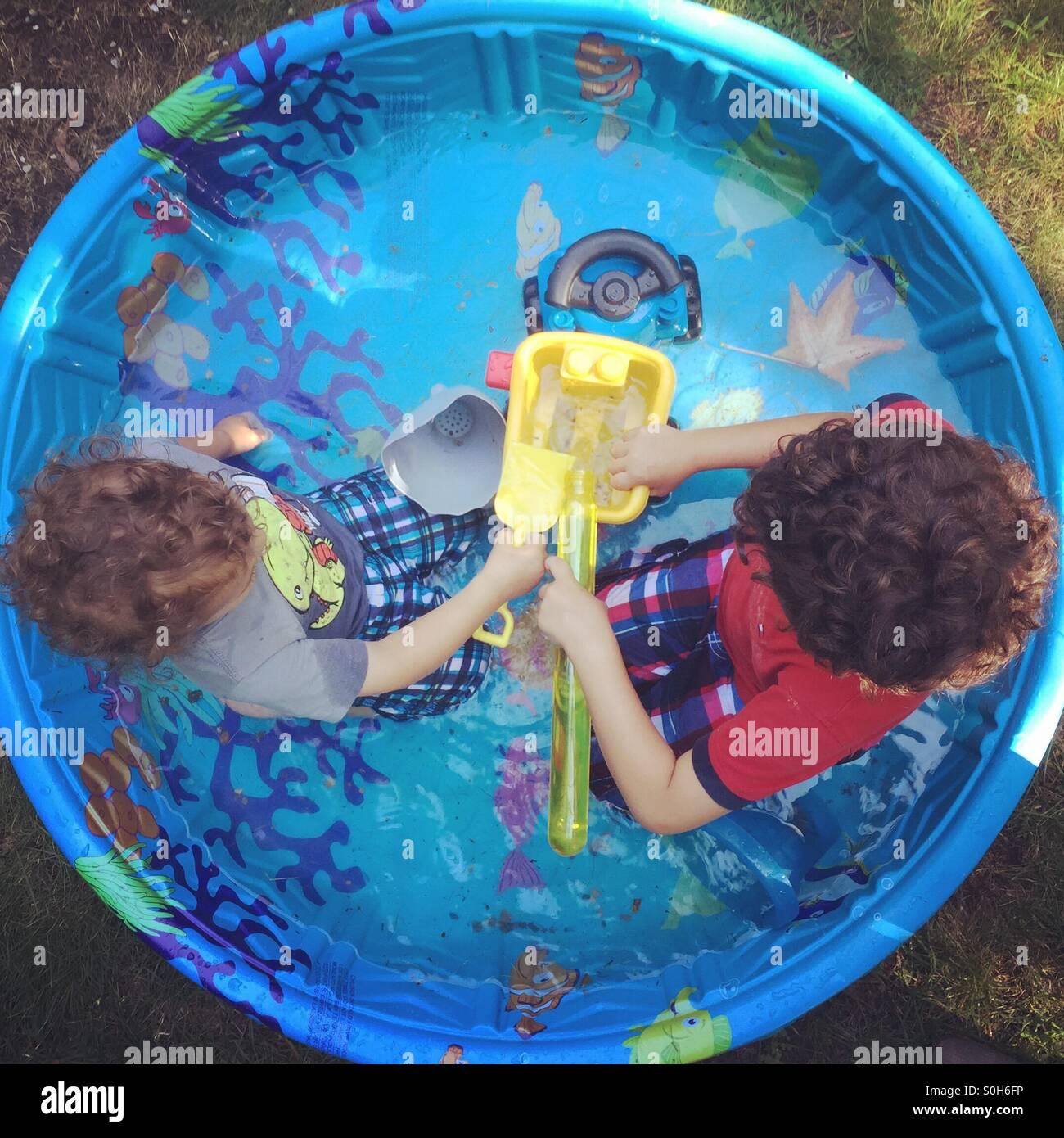 Fratelli nella piscina per bambini Foto Stock
