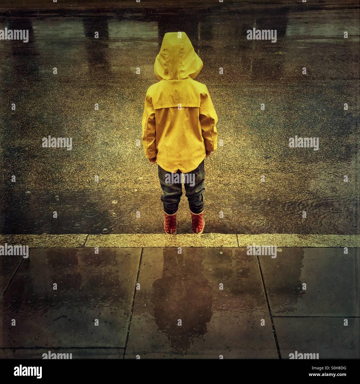 Bambino in piedi in una pozzanghera sotto la pioggia Immagini Stock