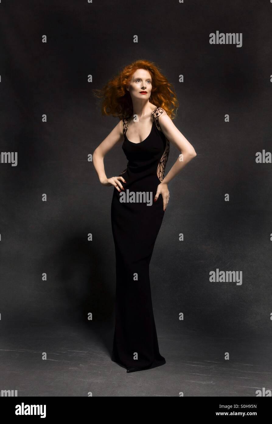 Redhead modello in Lungo abito nero in studio Immagini Stock