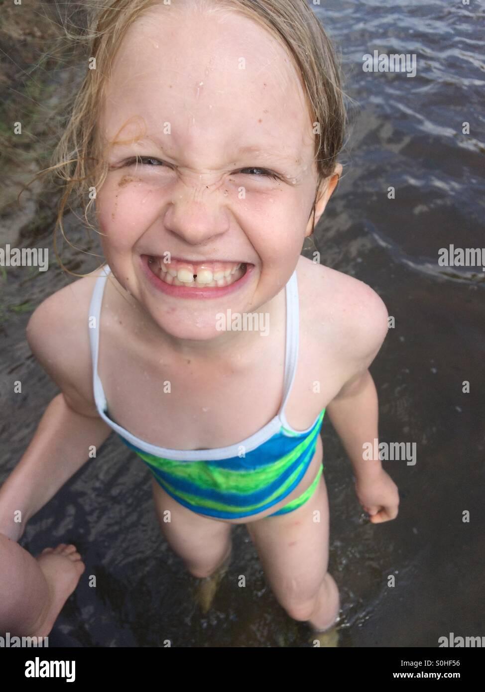 Giovane ragazza sorridente e divertirsi afferrando il suo fratello è la gamba nel fiume Immagini Stock