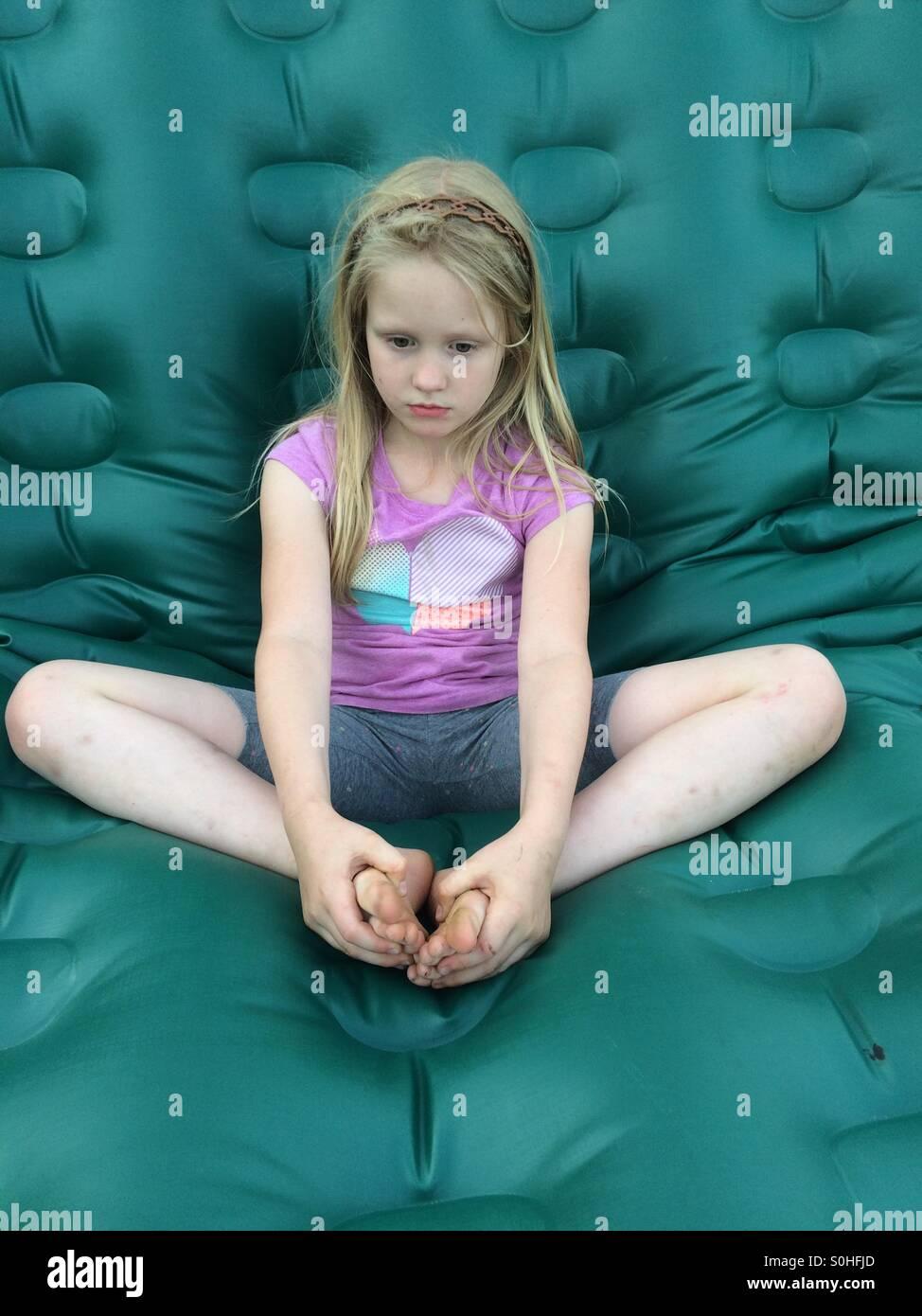 Malinconici ragazza seduta su un materasso verde Immagini Stock