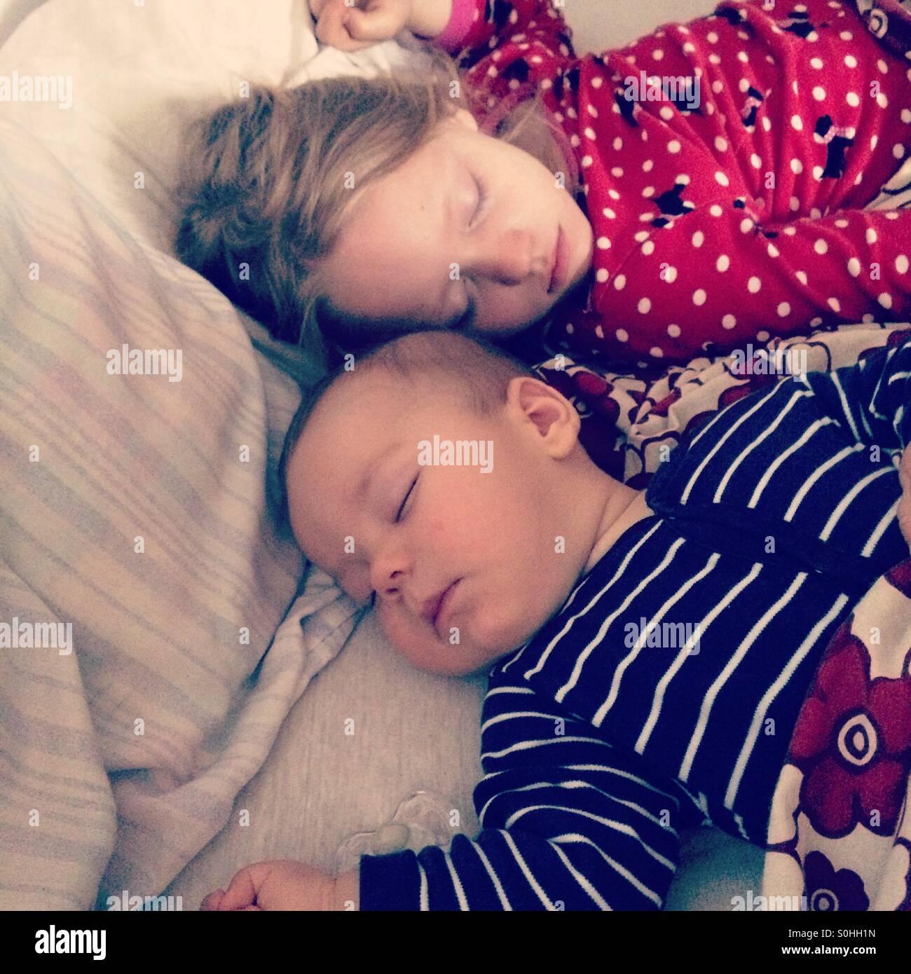 Due bambini dormono insieme pacificamente in letto con i genitori Immagini Stock