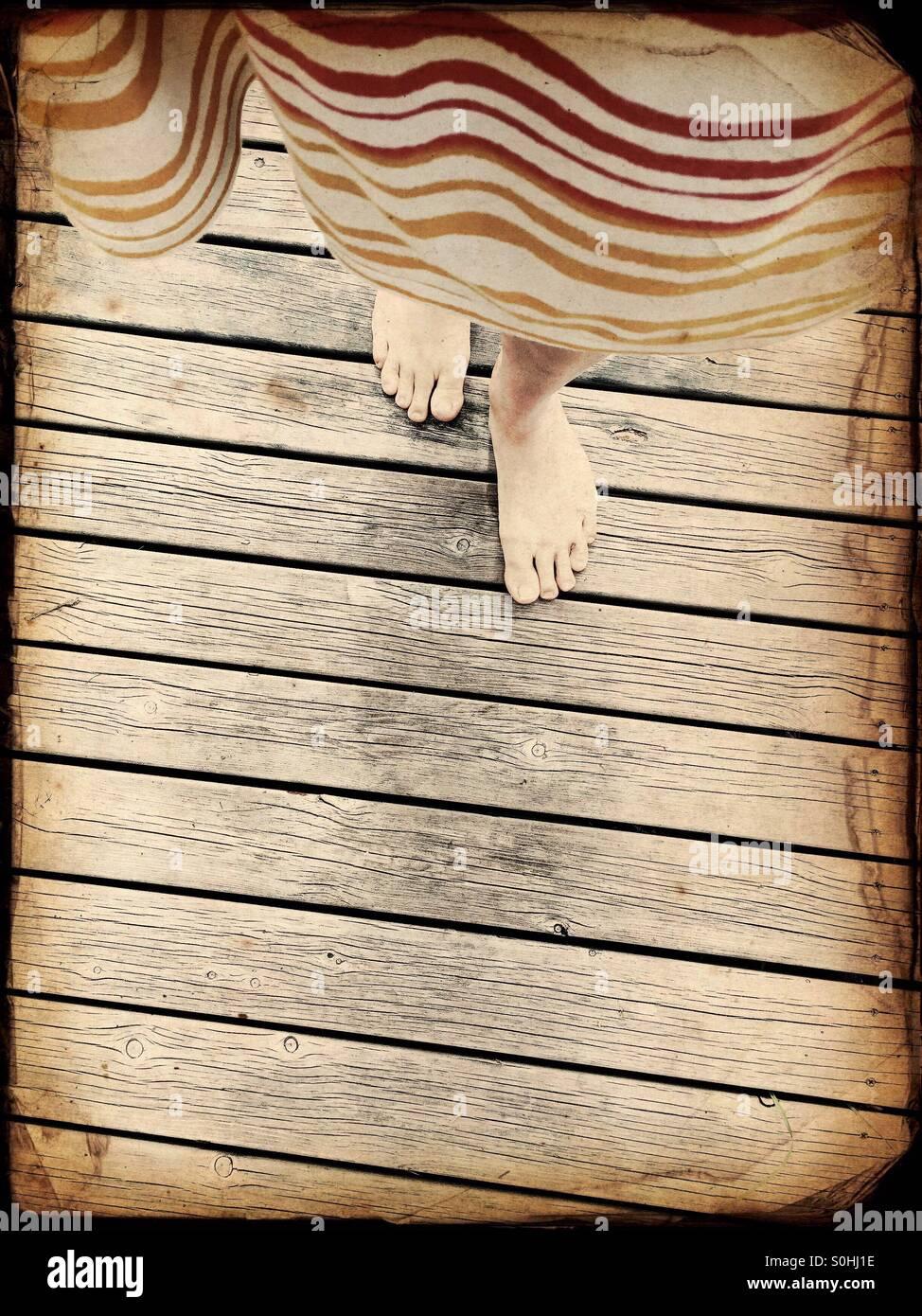Una donna che cammina un molo in legno in estate cottage, Finlandia Immagini Stock