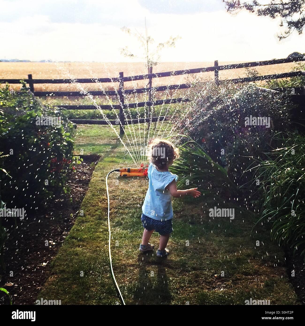 Bambina giocando con sprinkler REGNO UNITO Foto Stock