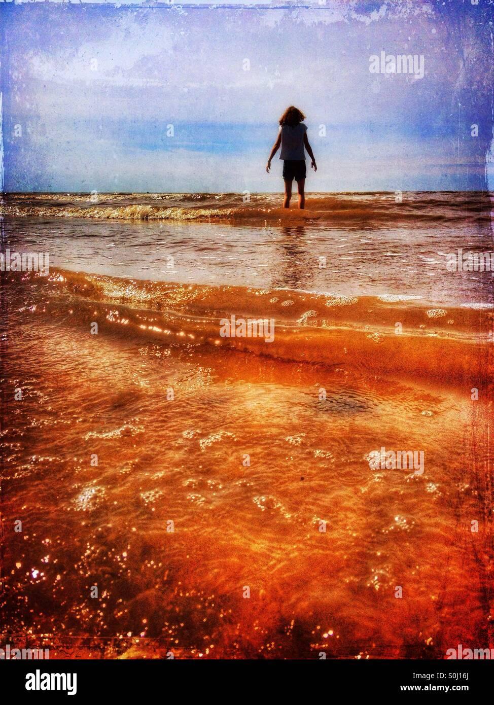 Ragazza giovane paddling in mare Immagini Stock