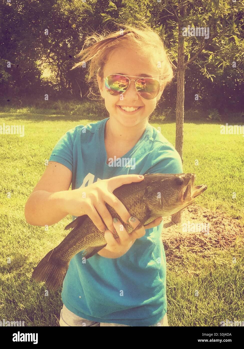 Giovane ragazza tenendo un Largemouth Bass ha catturati durante la pesca Immagini Stock