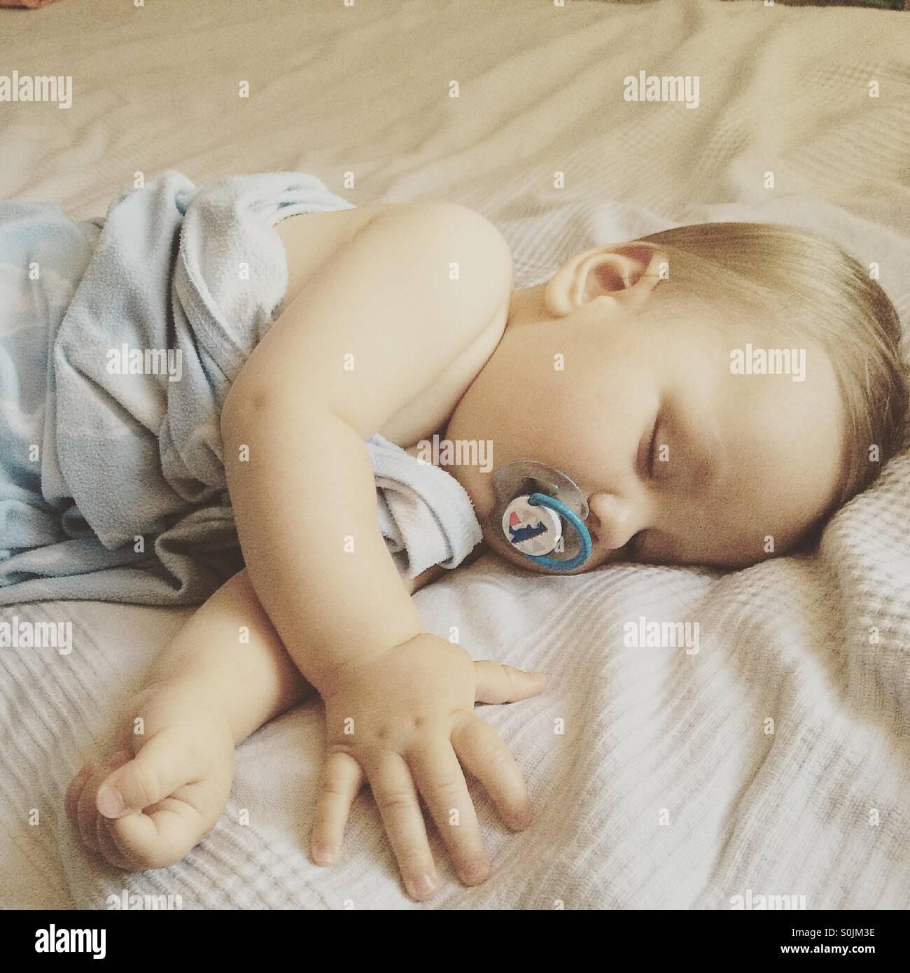 8 mese fa bambino dorme tranquillamente in una calda giornata estiva sui genitori letto ricoperto con una luce blu, Immagini Stock