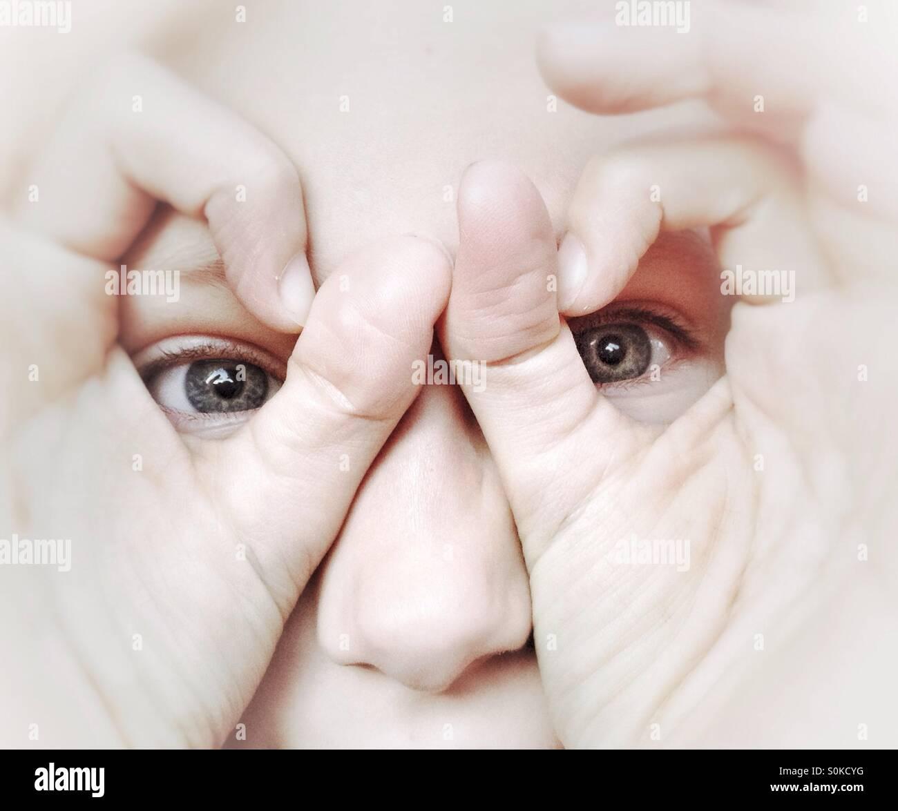 Ragazza giovane cerca attraverso occhiali realizzati dalla sua dita Immagini Stock