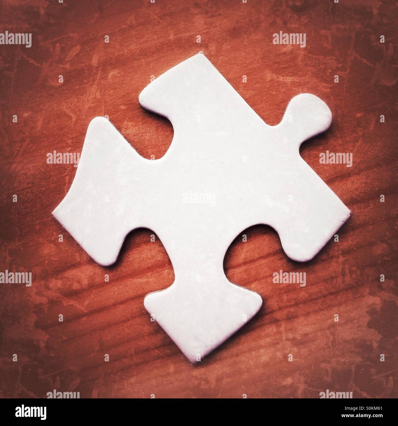 Schermata bianca vuota puzzle pezzo su una superficie in legno con grunge effetti di filtro Immagini Stock