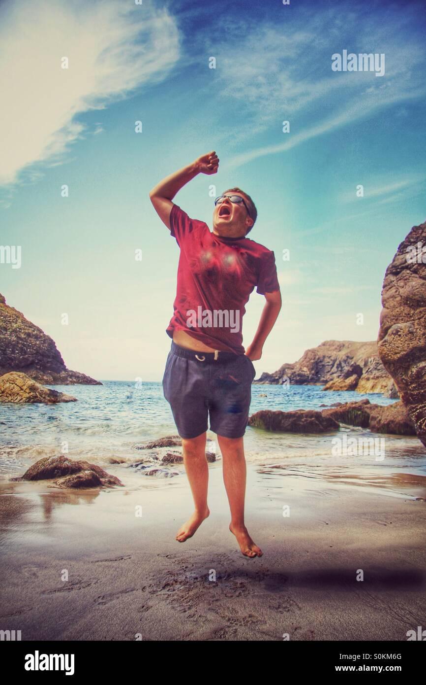 Un ragazzo su una spiaggia di sabbia a salti di gioia. Un Cornish beach con l'oceano dietro di lui. Immagini Stock