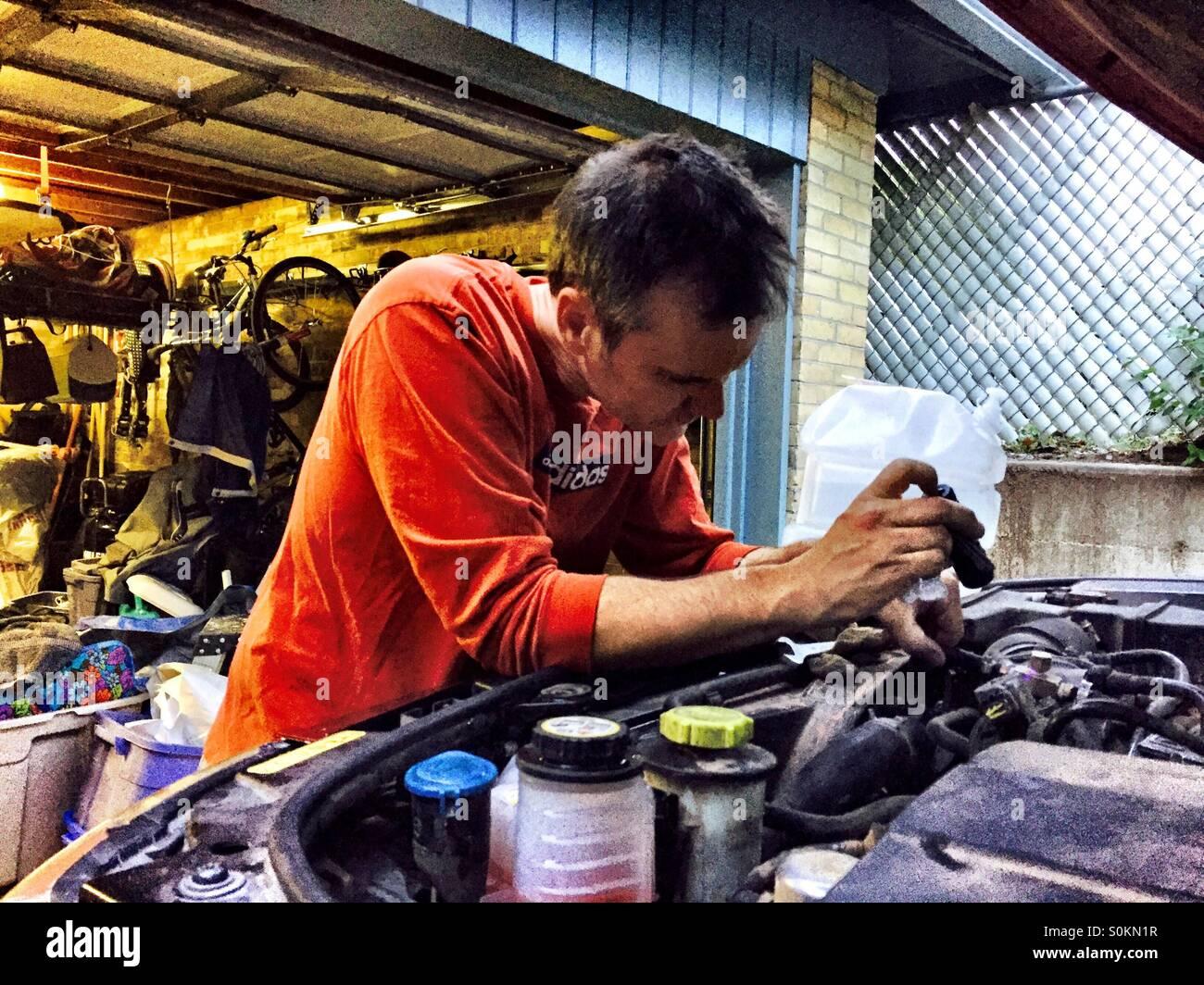 A shade tree mechanic risolve un auto a motore. Immagini Stock