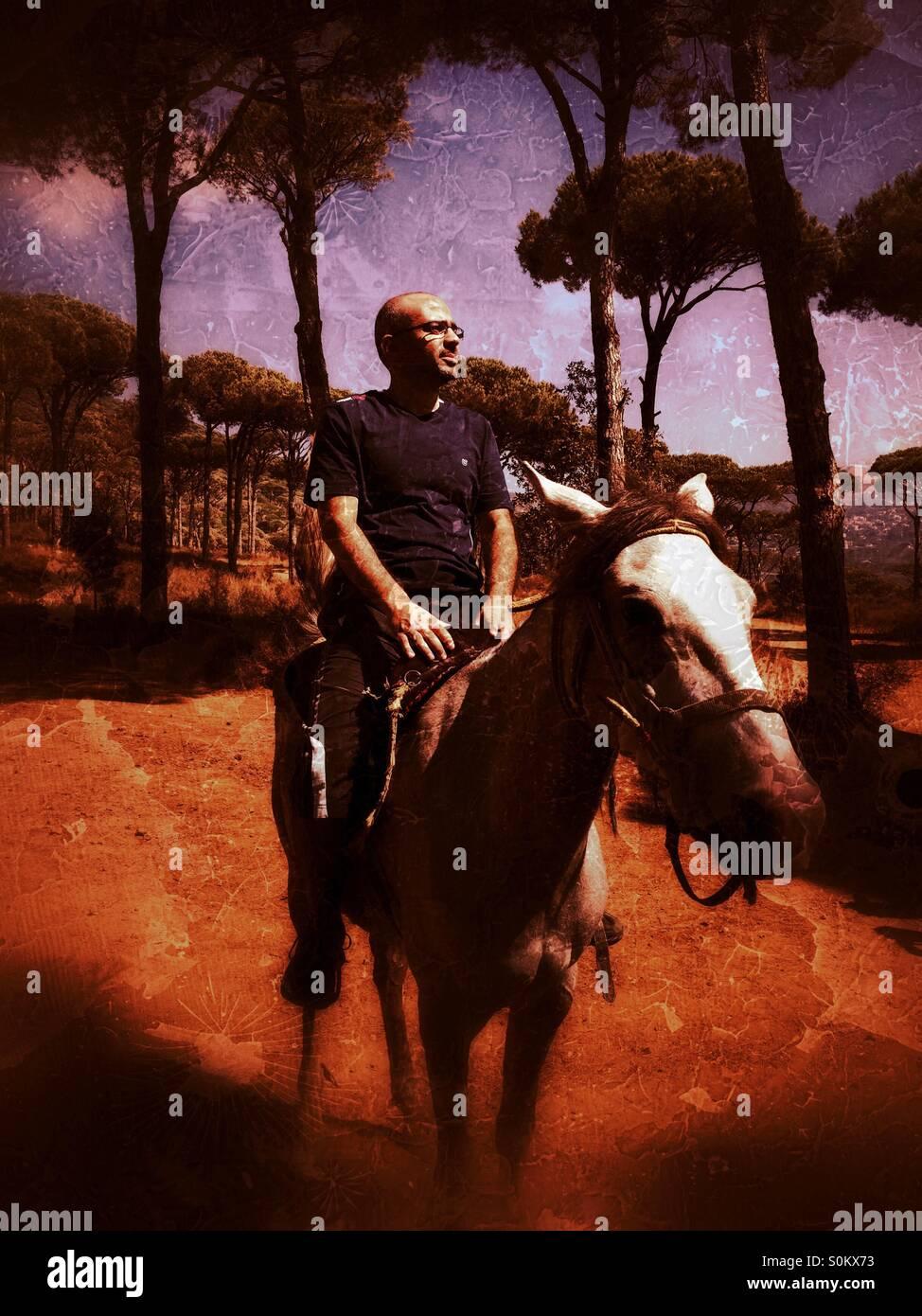 Uomo di mezza età in sella ad un cavallo con orgoglio nella foresta Immagini Stock