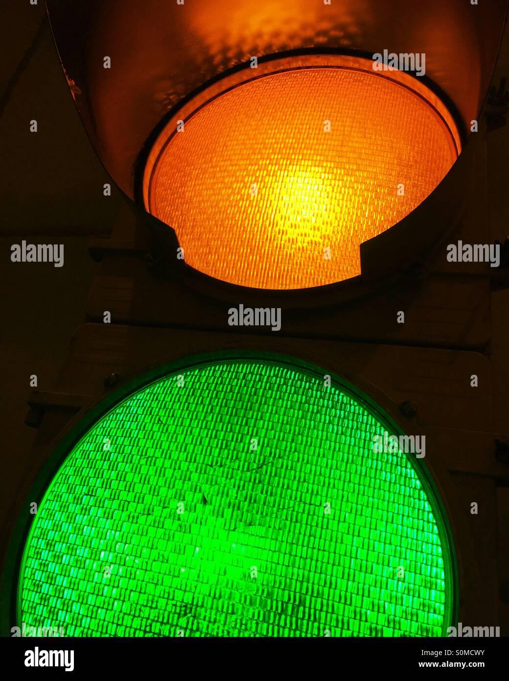 Close-up di illuminato in ambra gialla e verde segnali di traffico. Immagini Stock