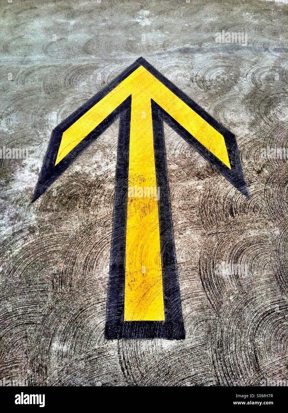Giallo freccia direzionale sul marciapiede in struttura di parcheggio Immagini Stock