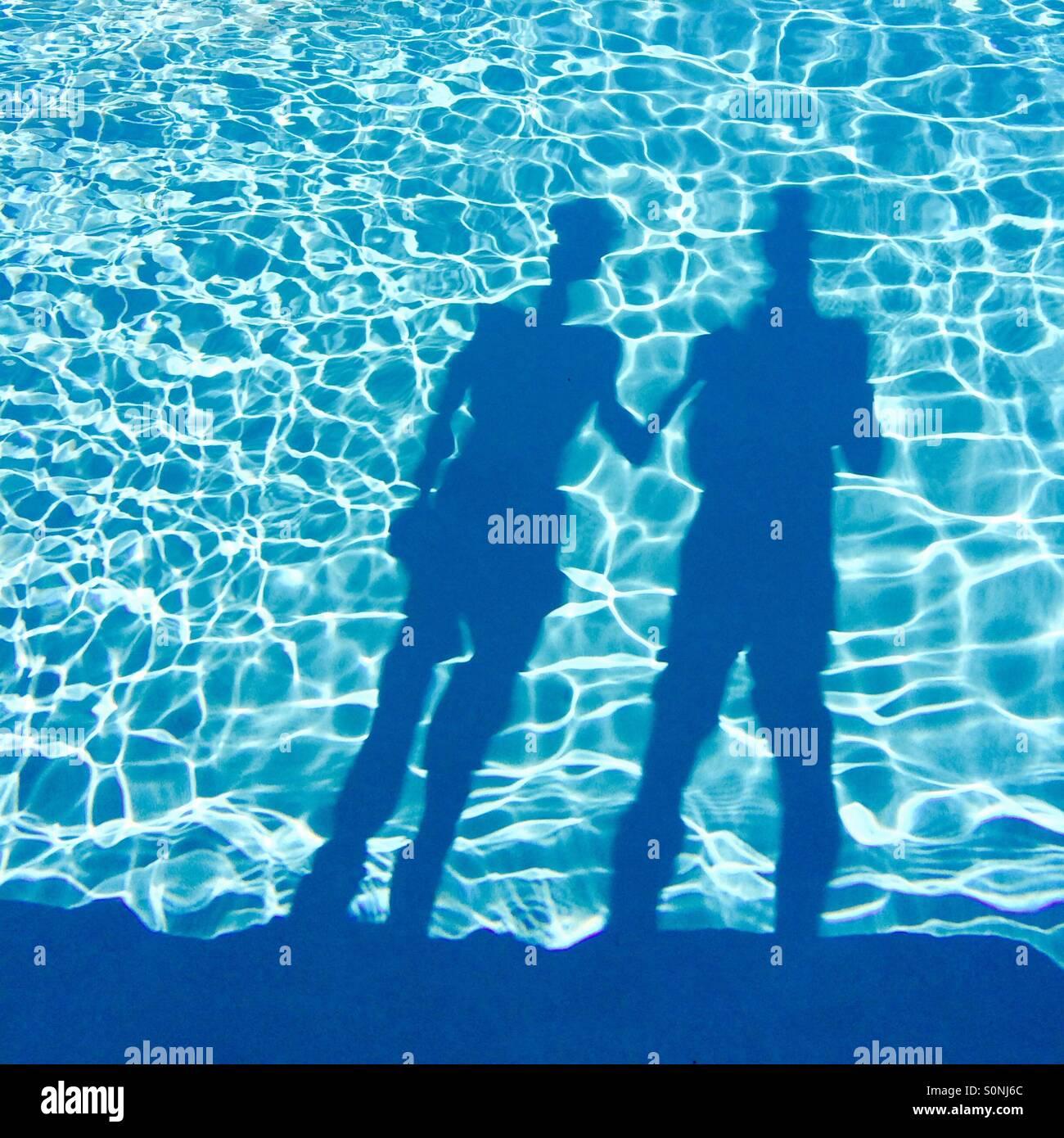 Ombra di una coppia in vacanza in piedi accanto a una piscina. Immagini Stock