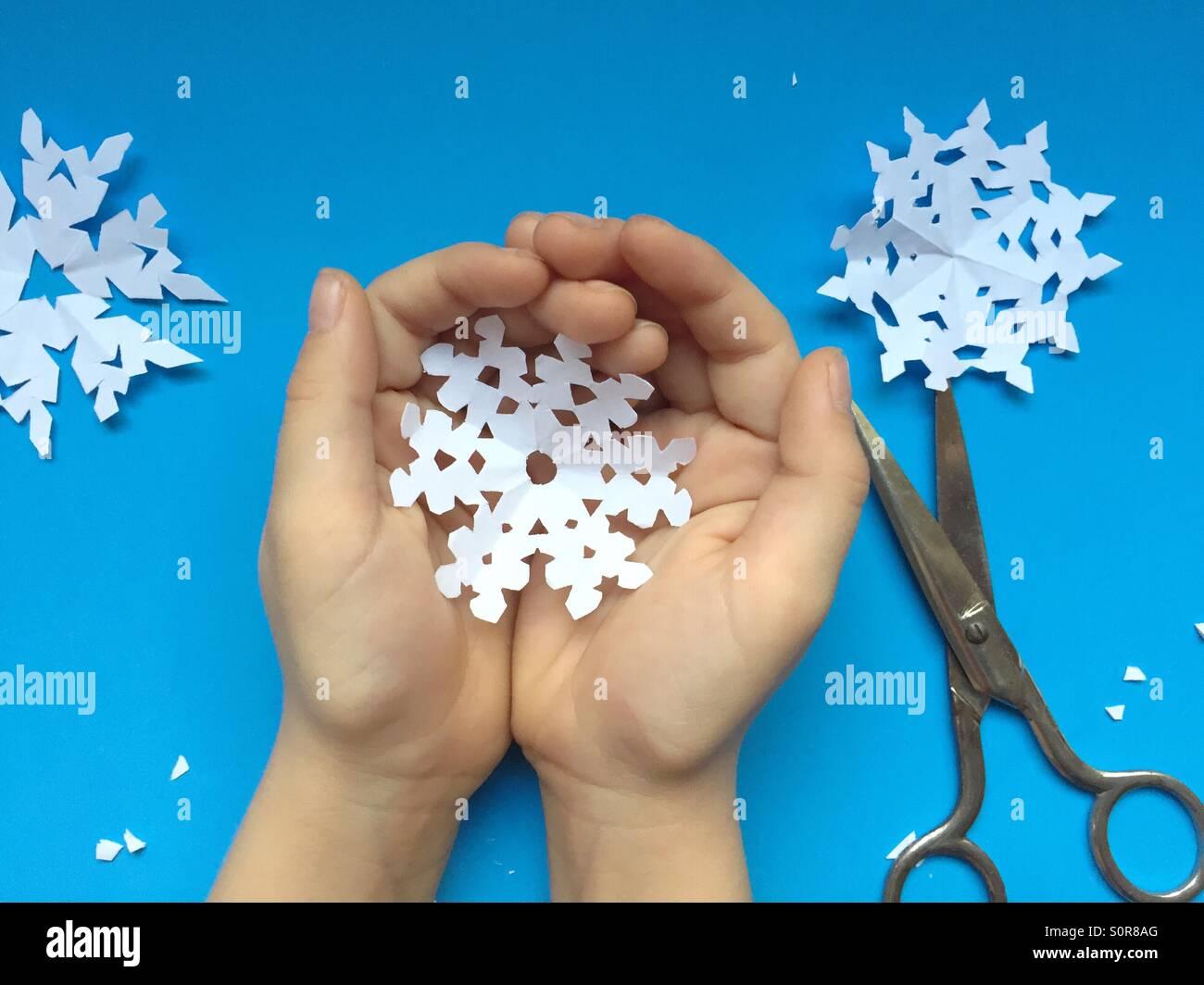 Bambino tiene il simbolo del fiocco di neve di carta Immagini Stock