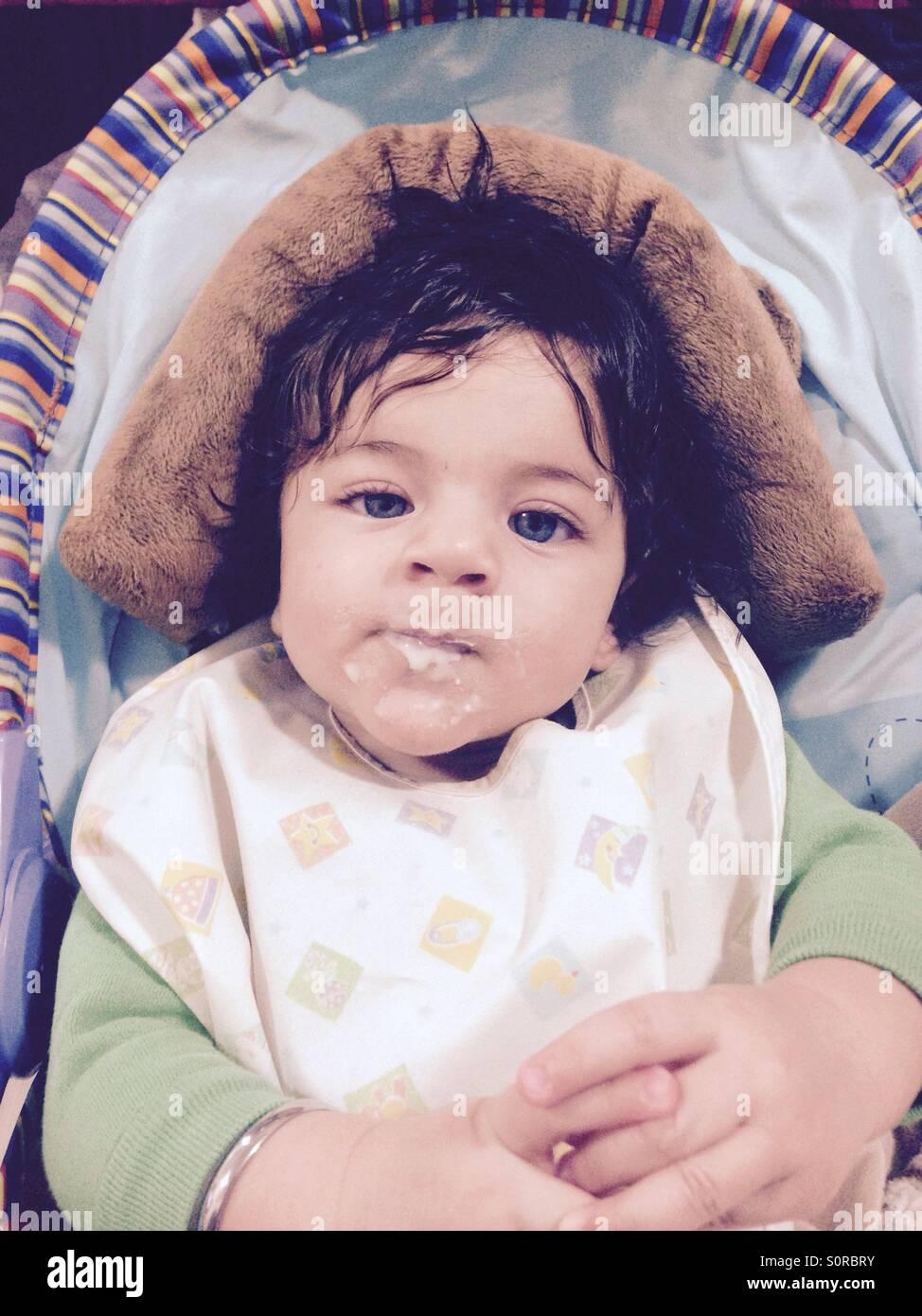 Baby boy dopo aver mangiato il suo primo momento di cereali. Immagini Stock