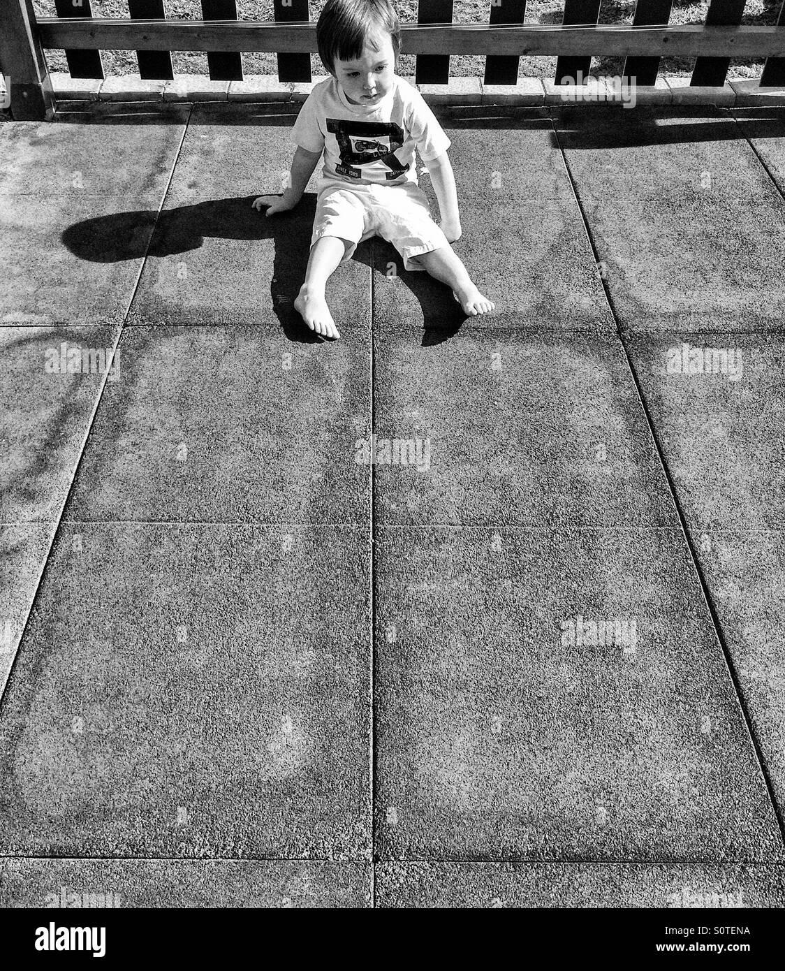 Ragazzo seduto da solo al sole Immagini Stock
