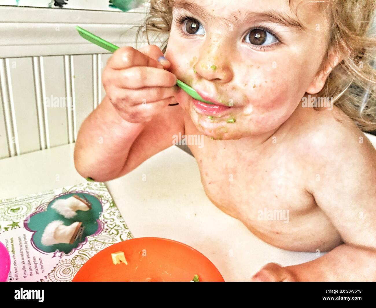 La mia bambina masticare le sue avocado. Immagini Stock